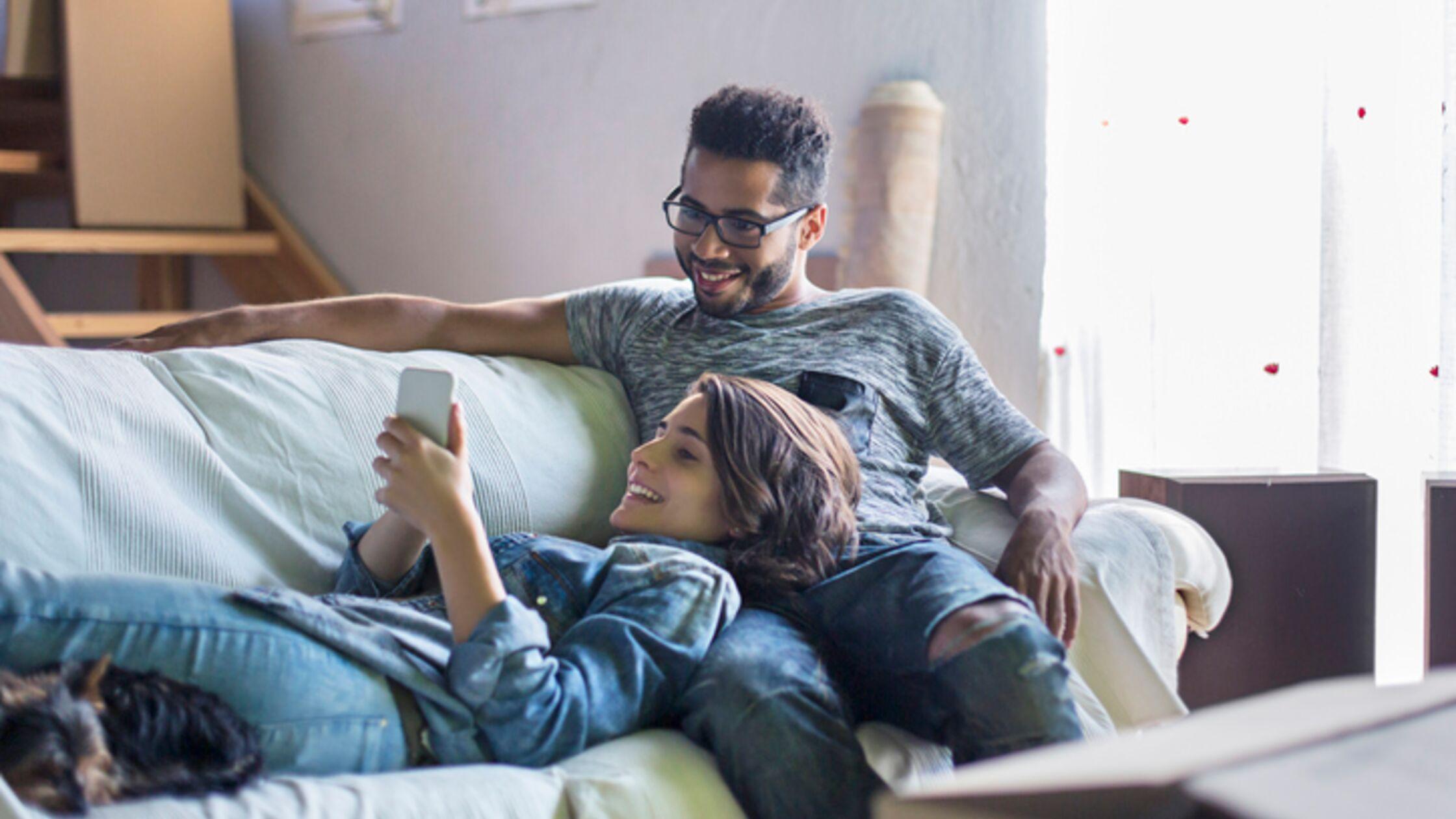 Paar ruht sich von Umzug auf dem Sofa aus.