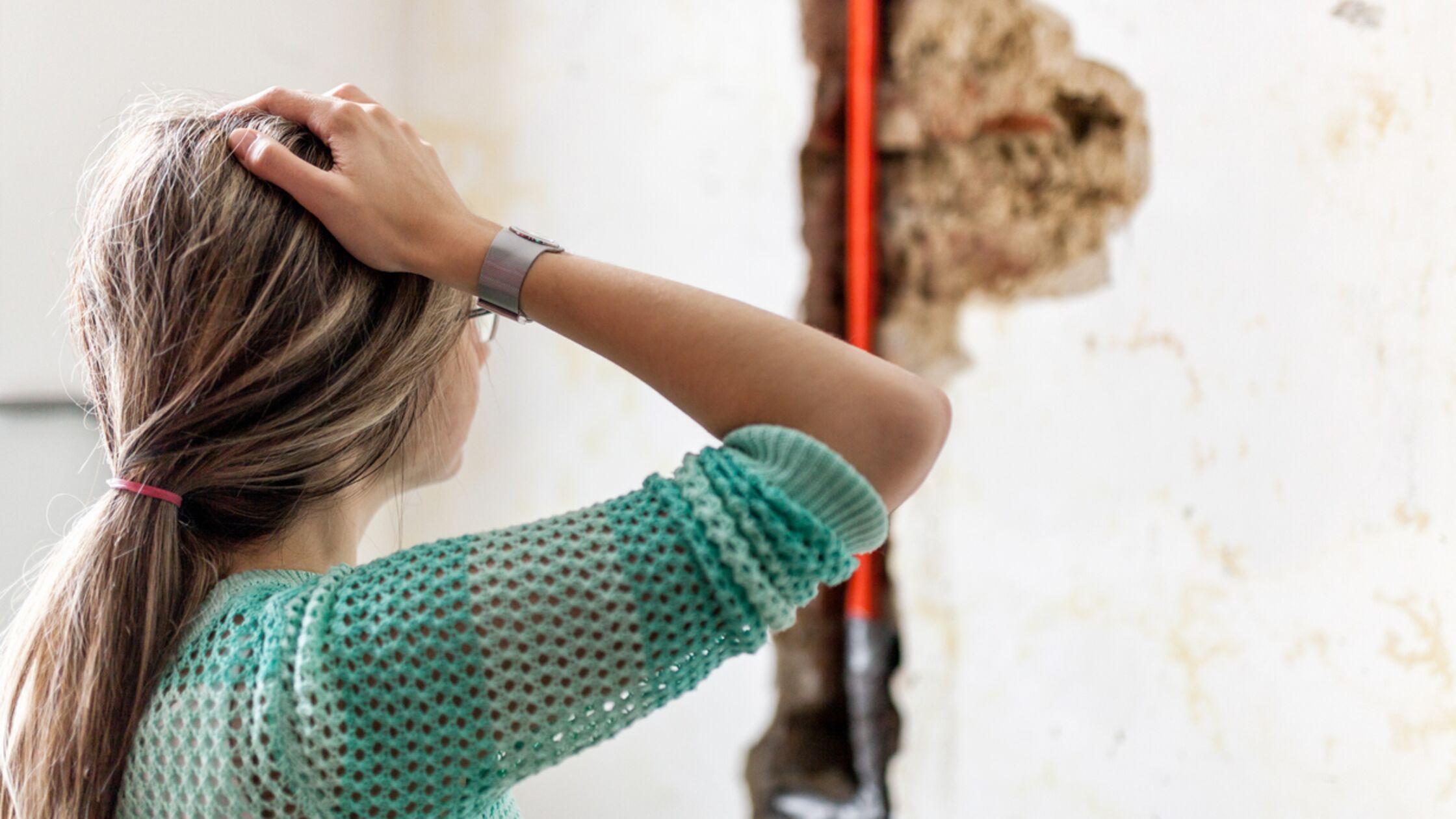 Frau vor beschädigter Wand