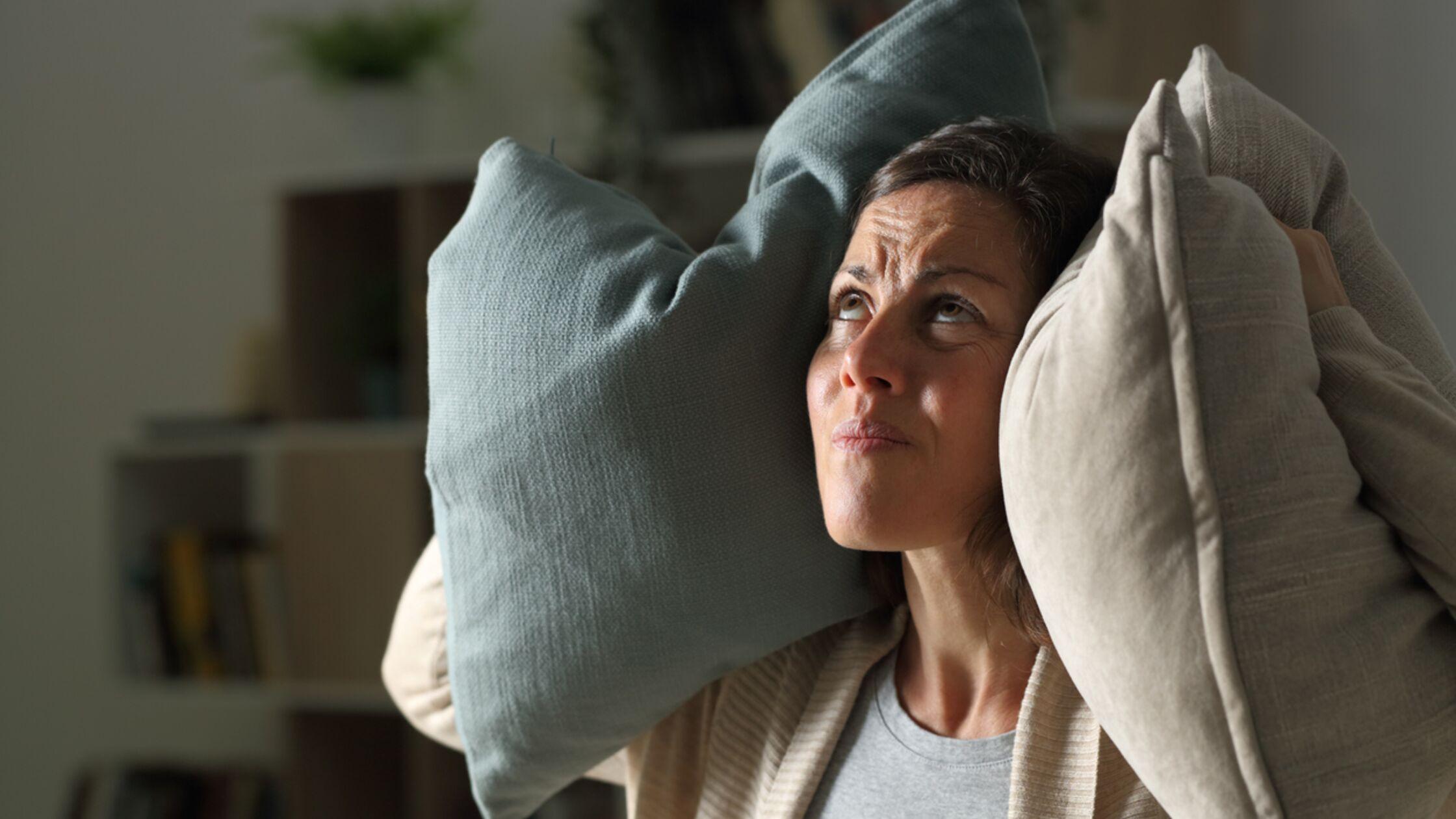 Frau hält sich Kissen vor die Ohren