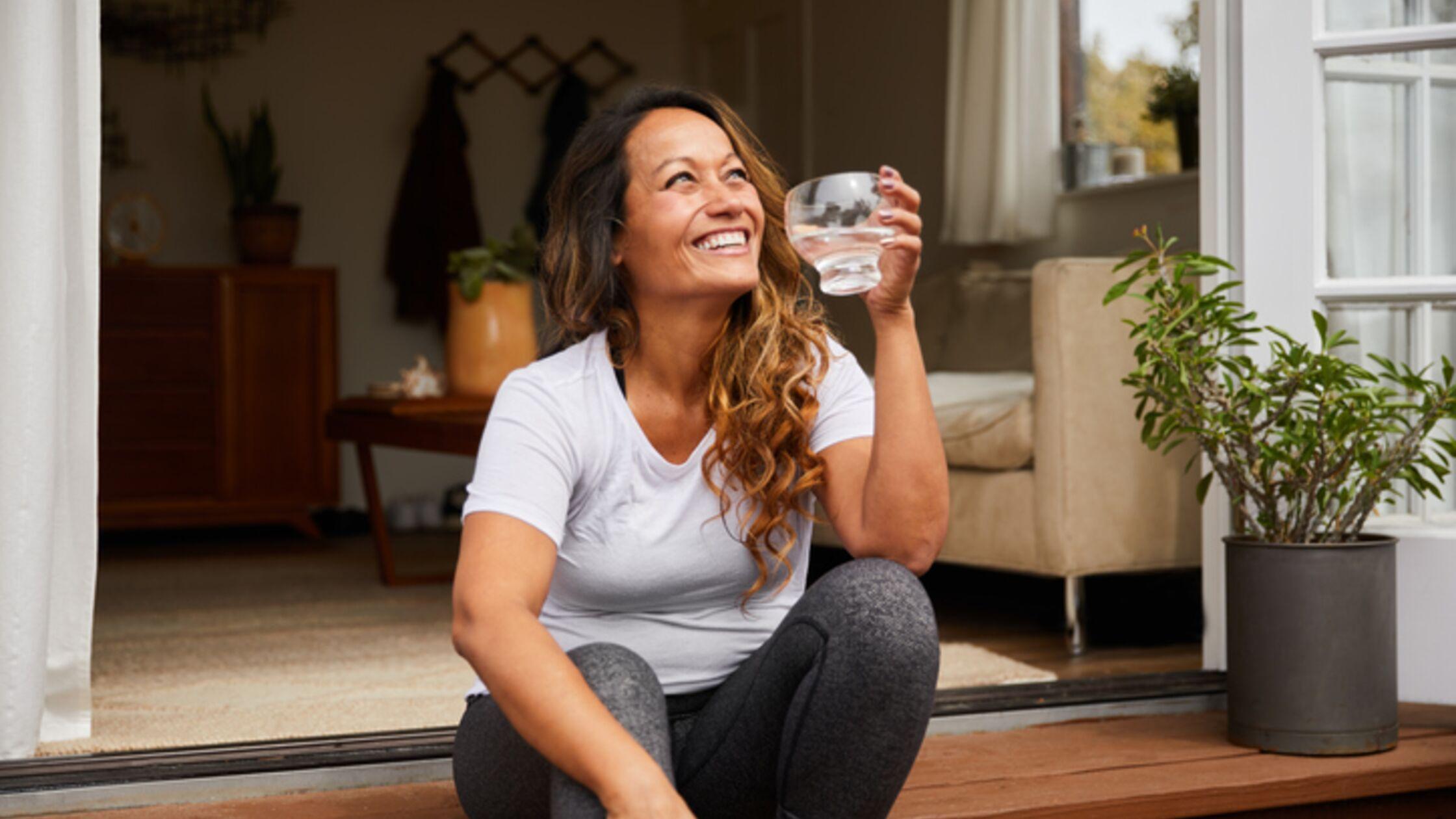 Lächelnde Frau trinkt Wasser