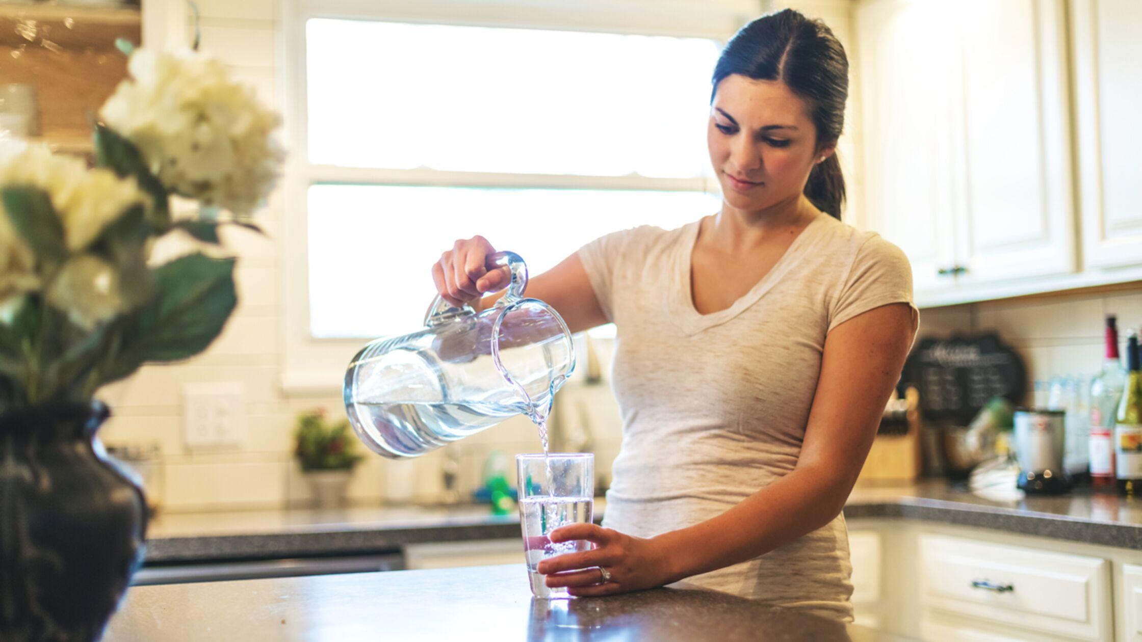 Frau schüttet Trinkwasser aus Karaffe in Glas