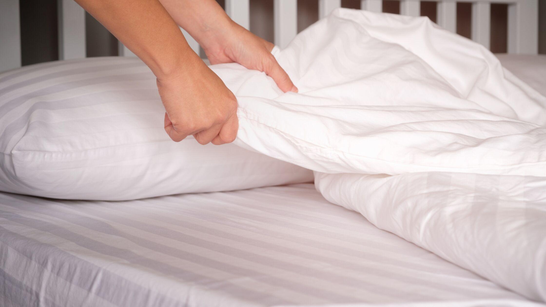 Mann wechselt Bettwäsche