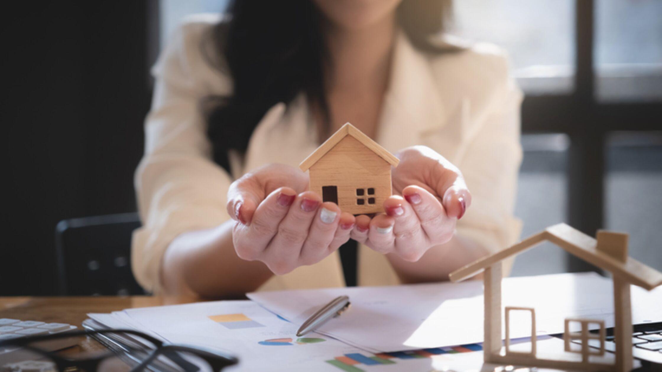 Frau hält kleines Haus schützend in den Händen