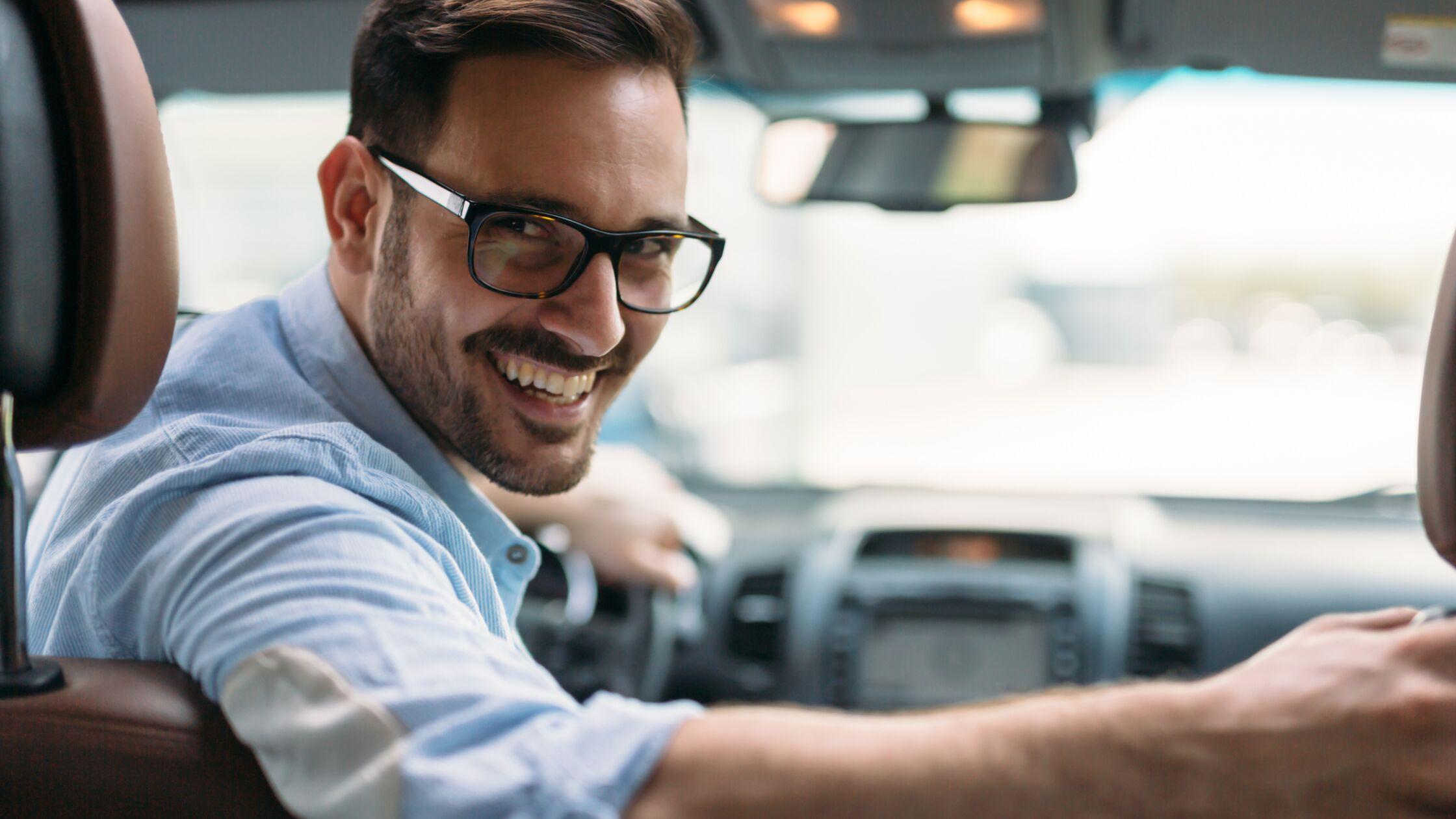 Mann sitzt lächelnd im Auto und schaut nach hinten