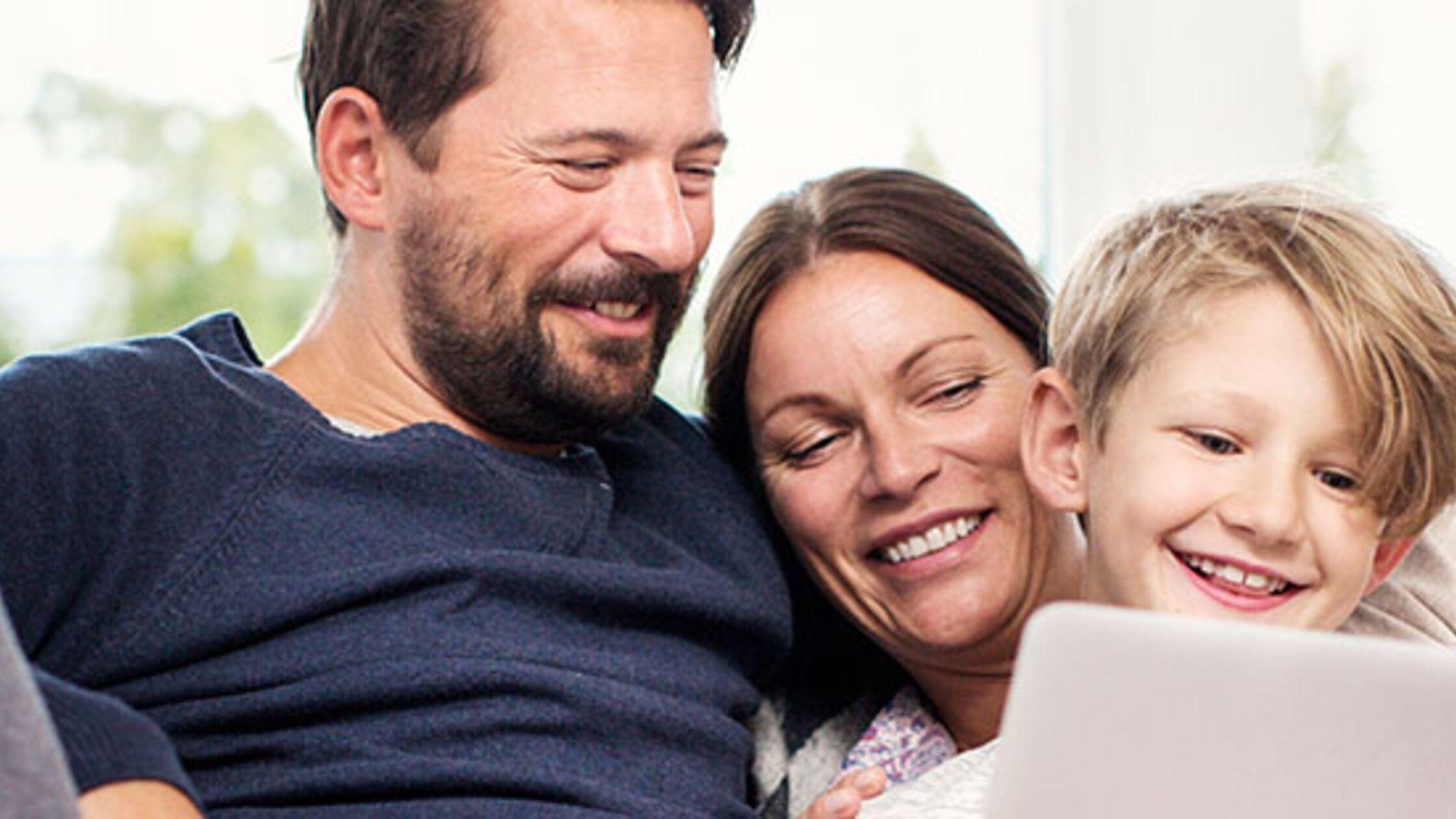 Mann, Frau und Kind schauen in einen Laptop