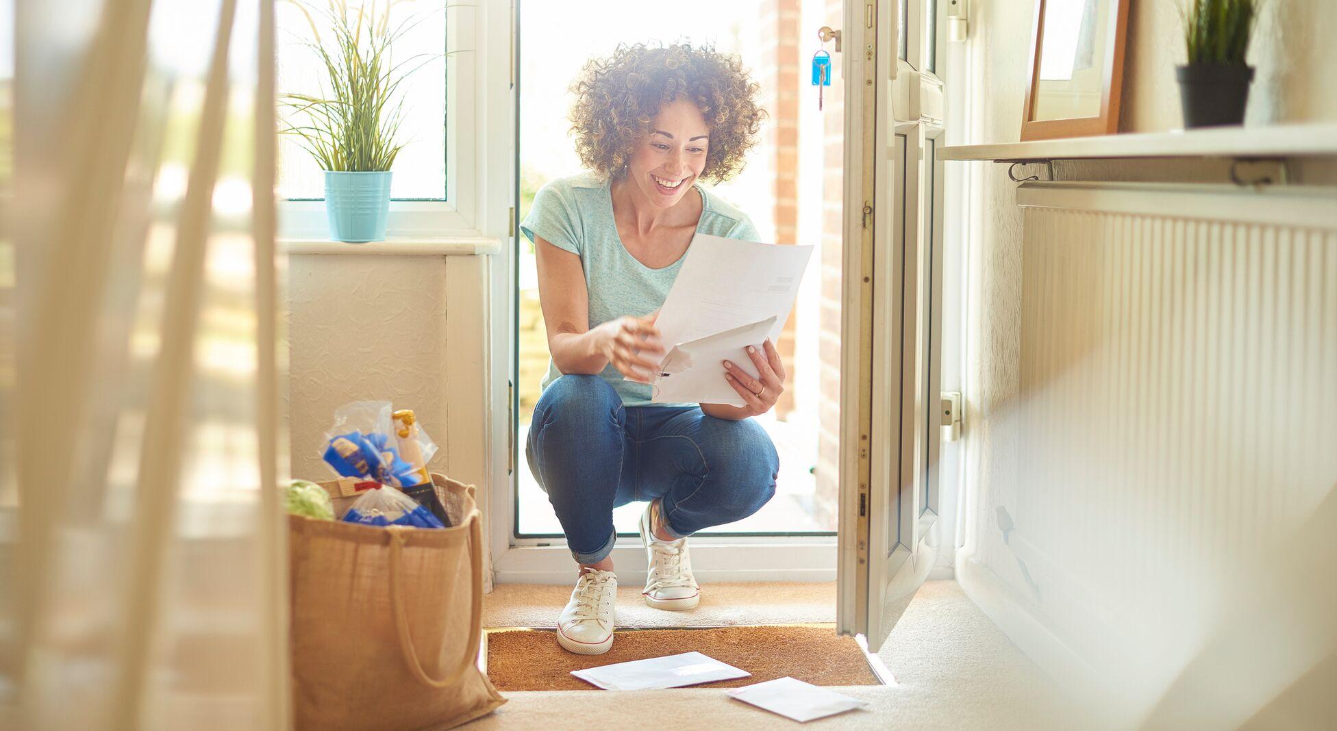 Nachsendeauftrag: Junge Frau öffnet Post an der Haustür.