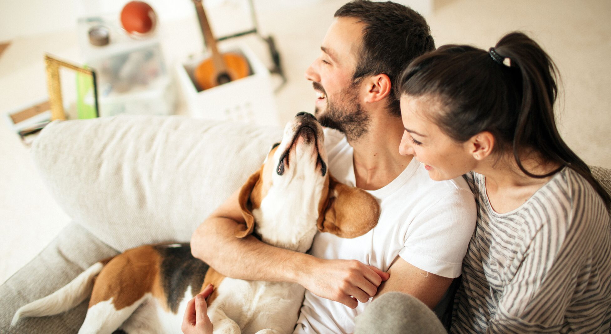 Paar mit Hund auf Couch.