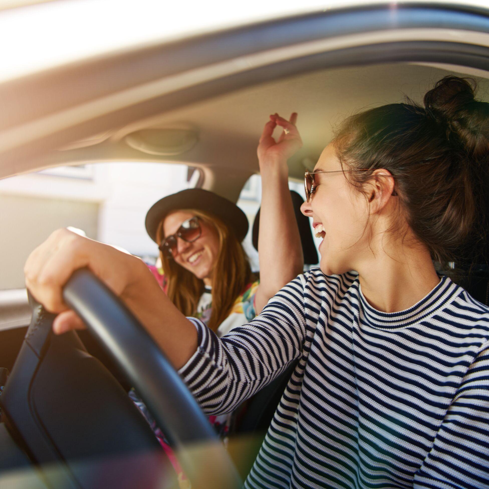 Zwei Frauen fahren glücklich Auto
