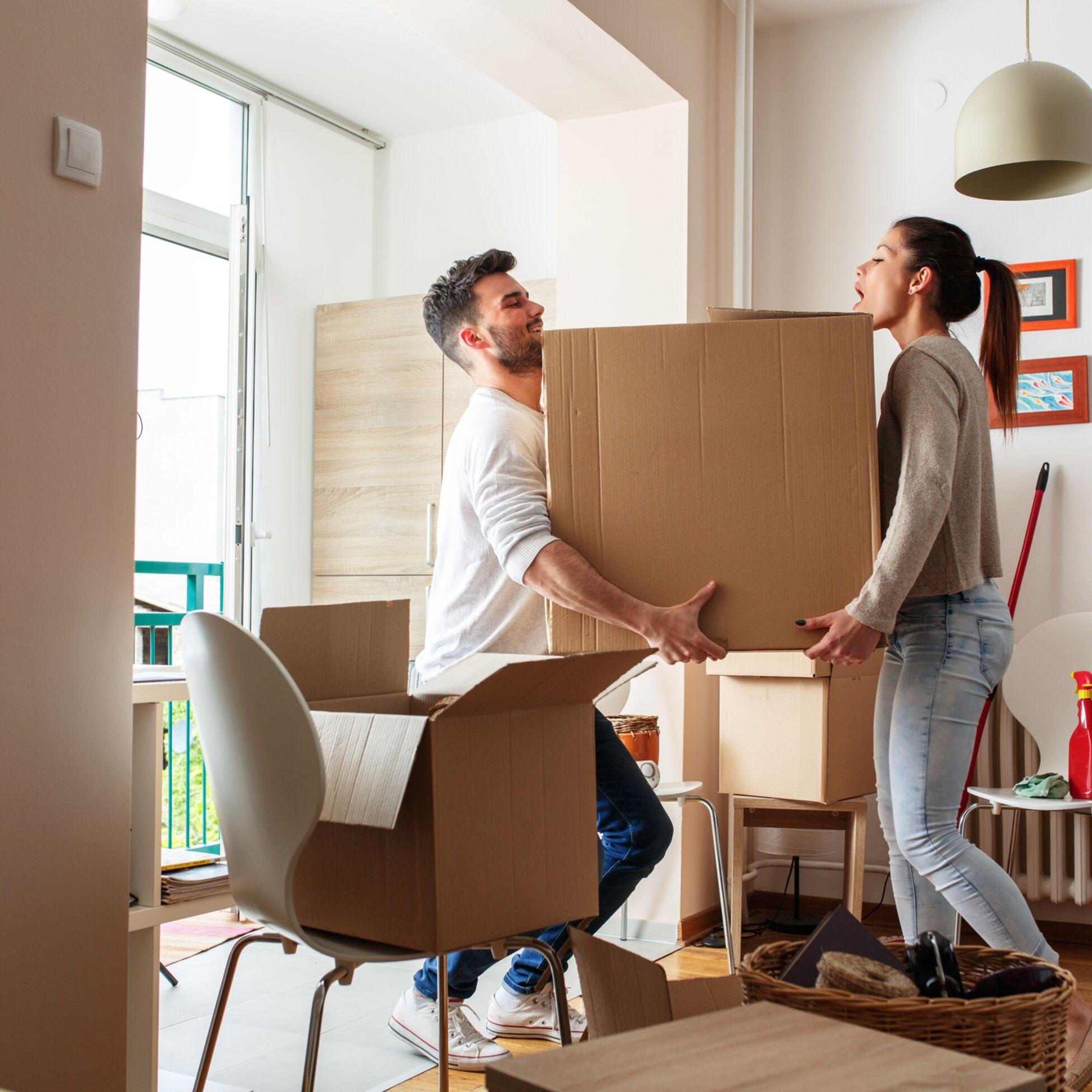 Junges Paar schleppt große Kiste zu zweit