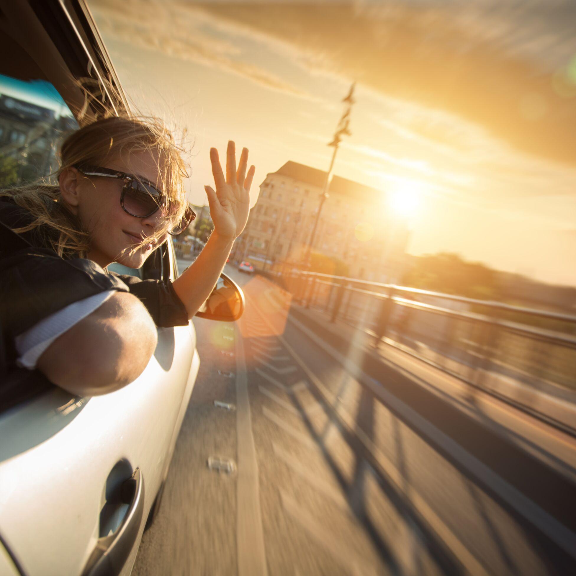 Junge Frau winkt aus geöffnetem Fenster eines fahrenden Autos.