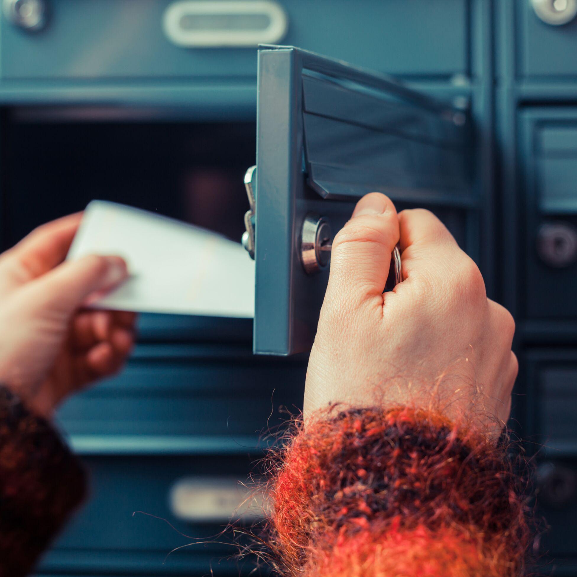 Person öffnet einen Briefkasten und nimmt Post heraus