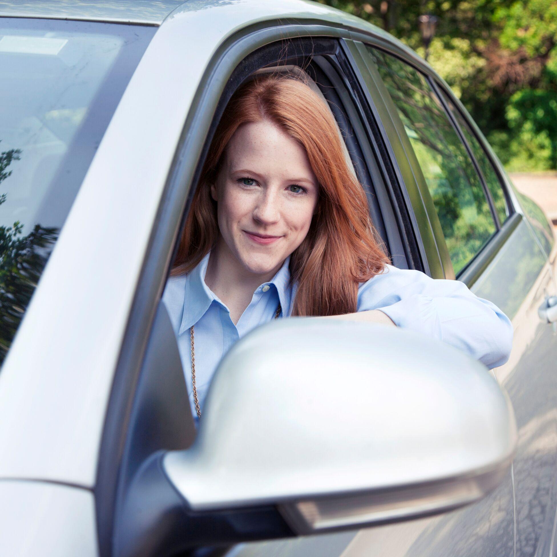 Frau am Steuer eines Wagens schaut aus dem Fenster