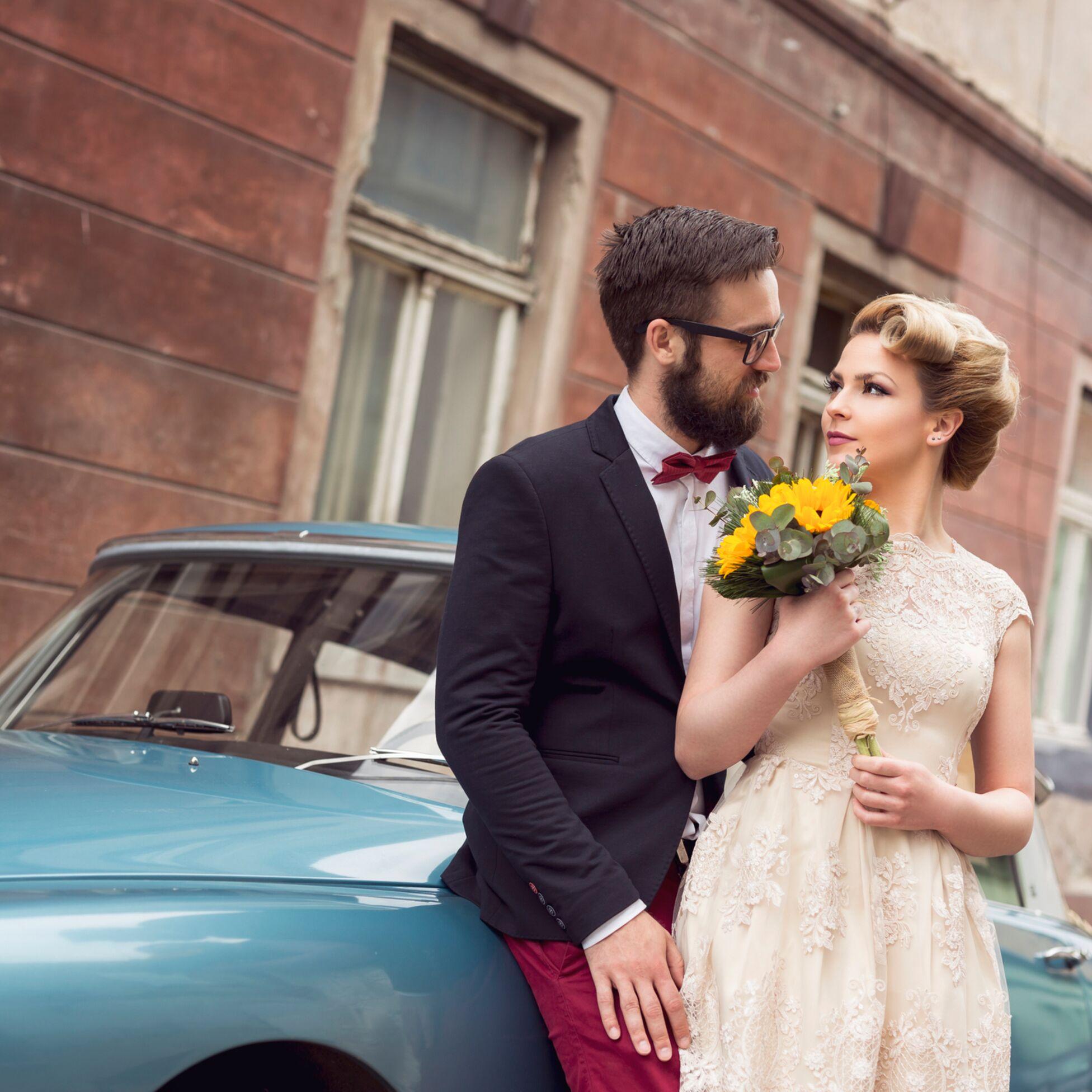 Hochzeitspaar steht vor Auto.