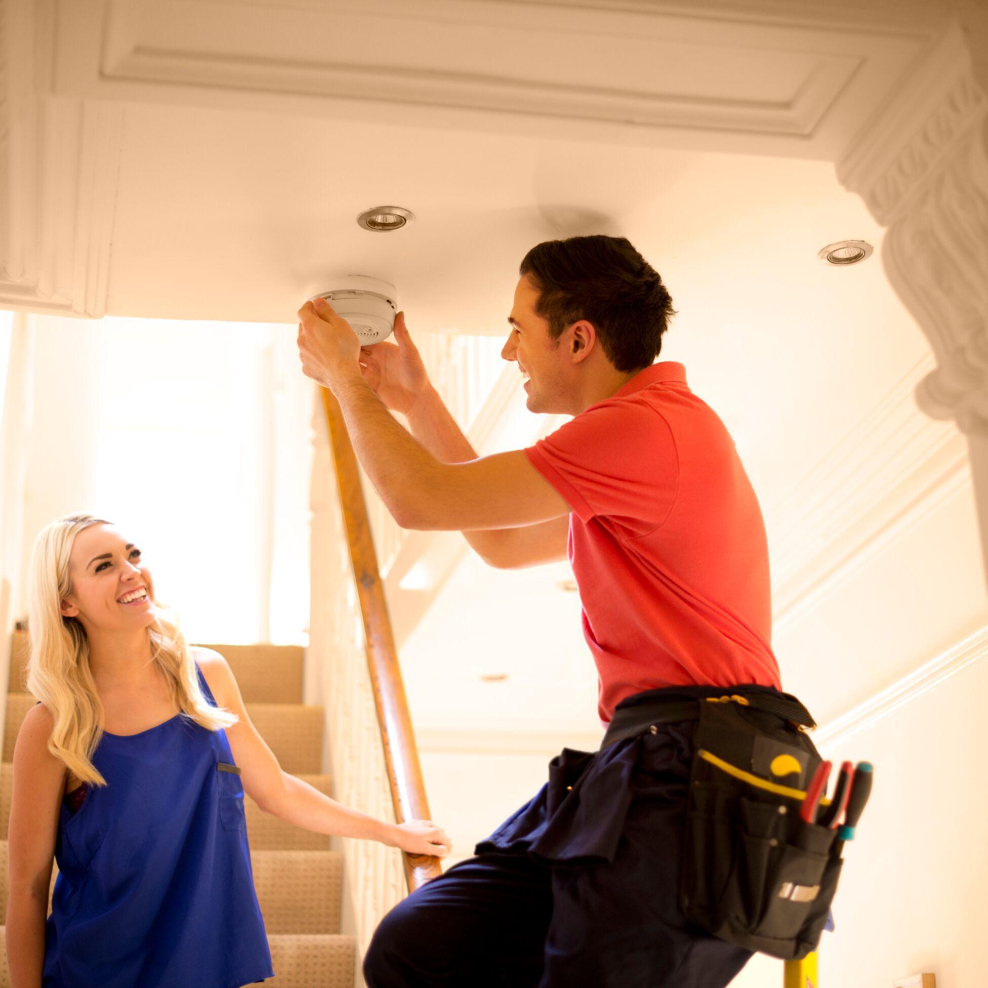 Mann hilft Frau beim Rauchmelder anbringen