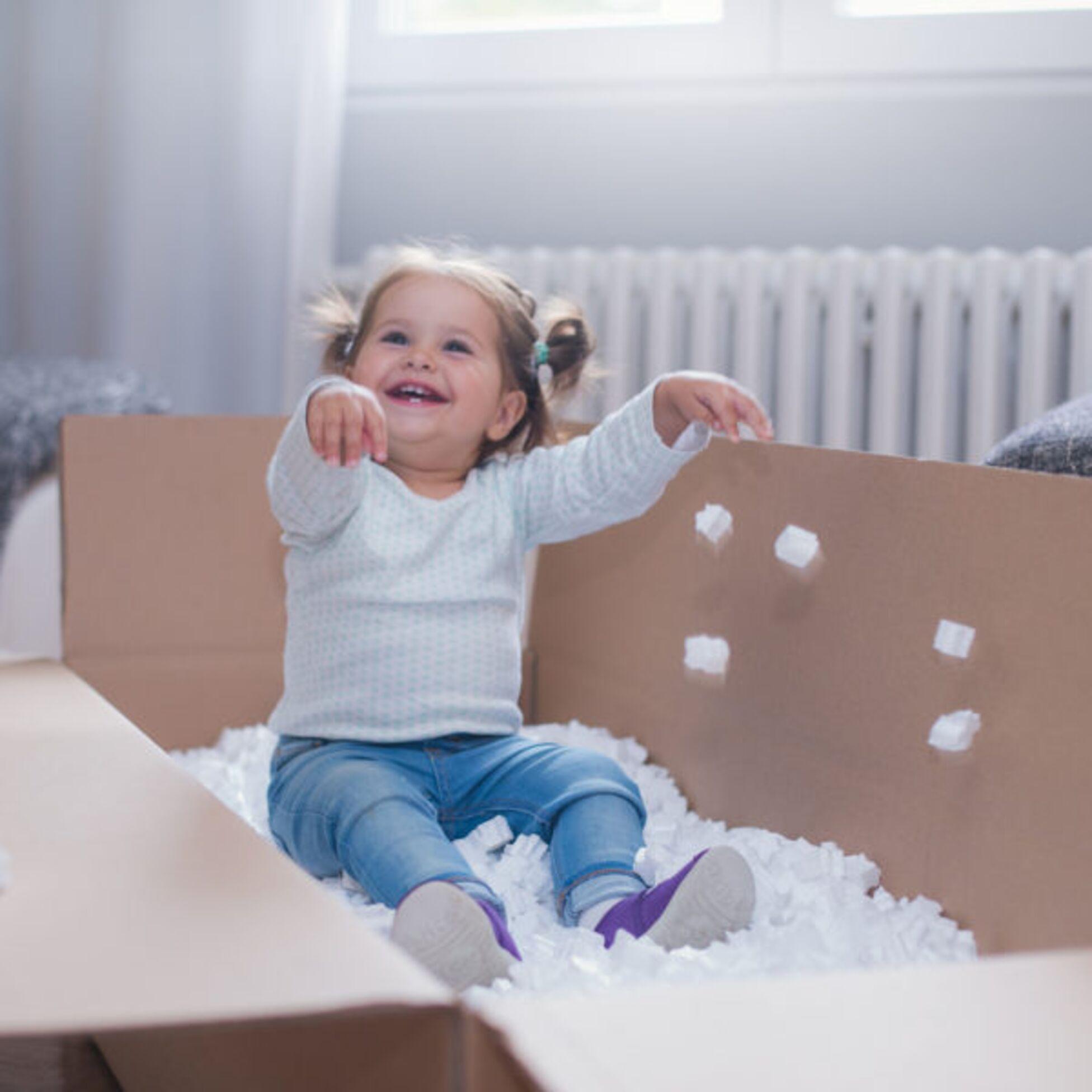Kleinkind spielt mit Verpackungsmaterial in Umzugskiste