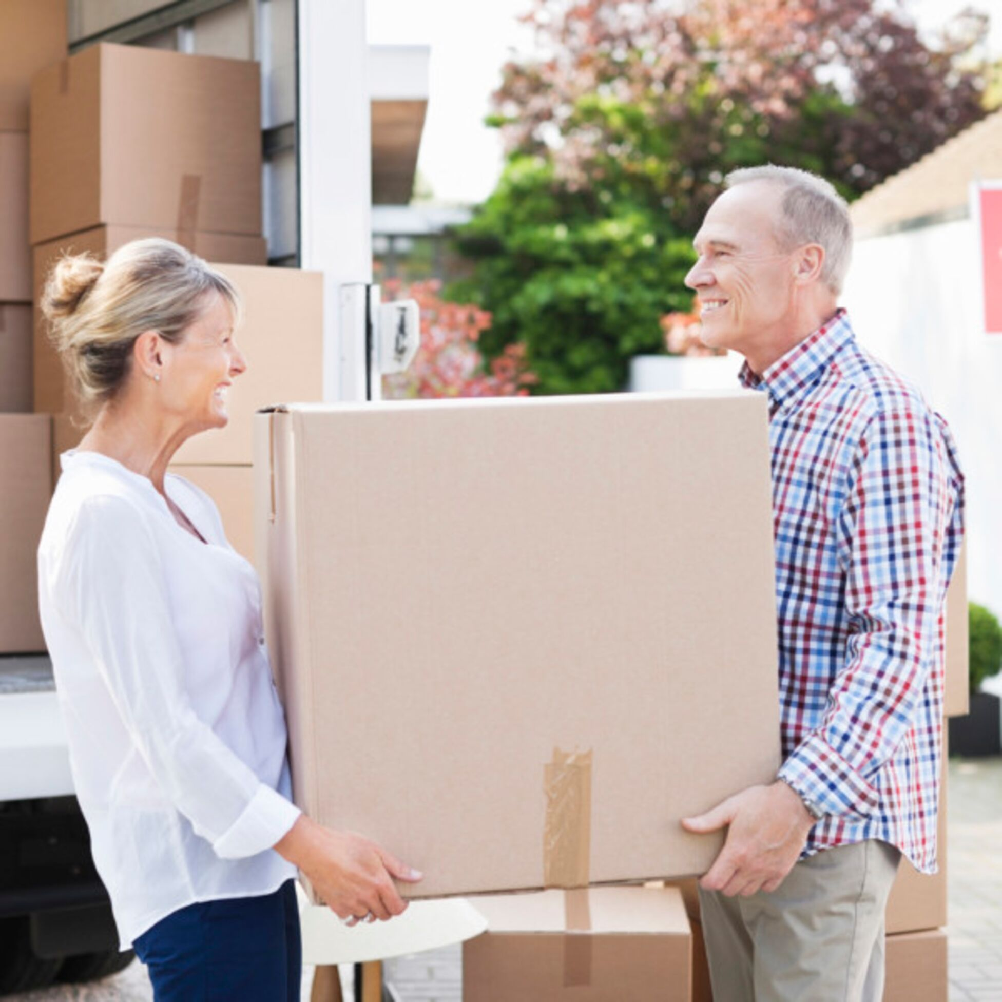 Älteres Paar transportiert Umzugskarton