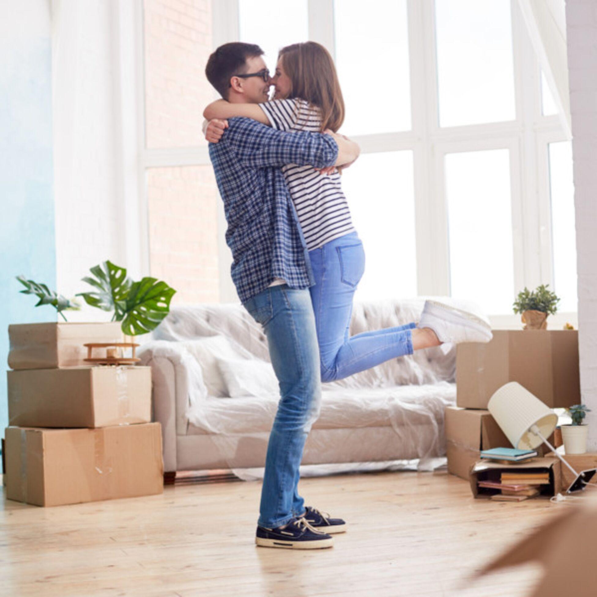Junges Paar umarmt sich zwischen Umzugskartons