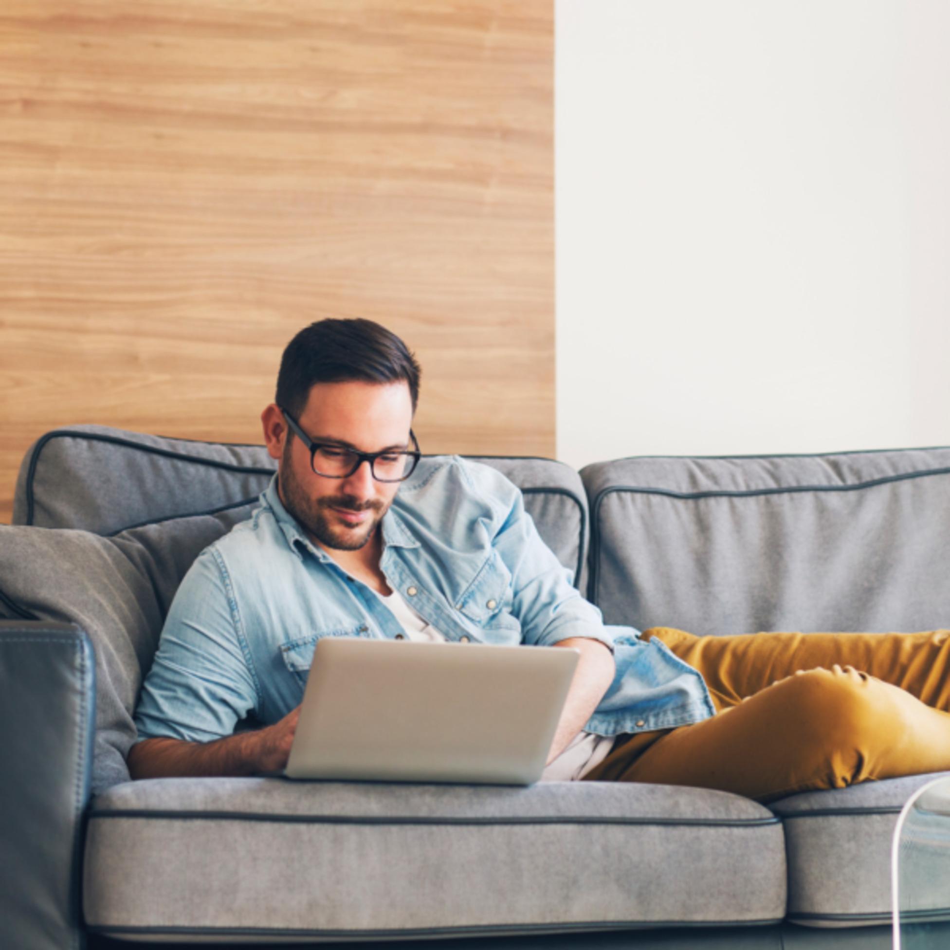 Mann mit Laptop auf Couch