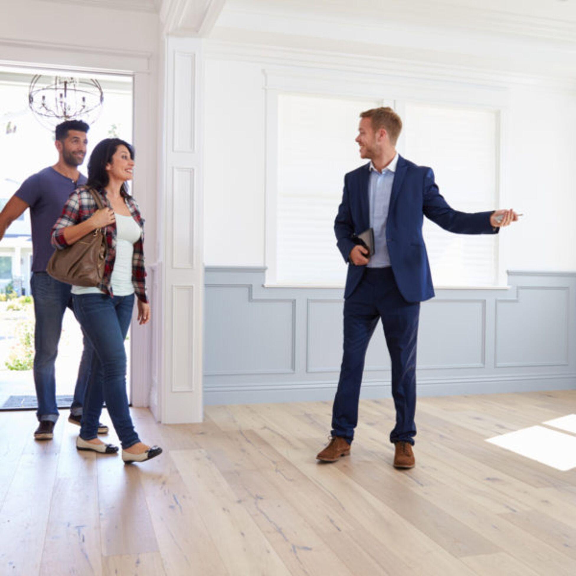 Makler zeigt Paar Wohnung