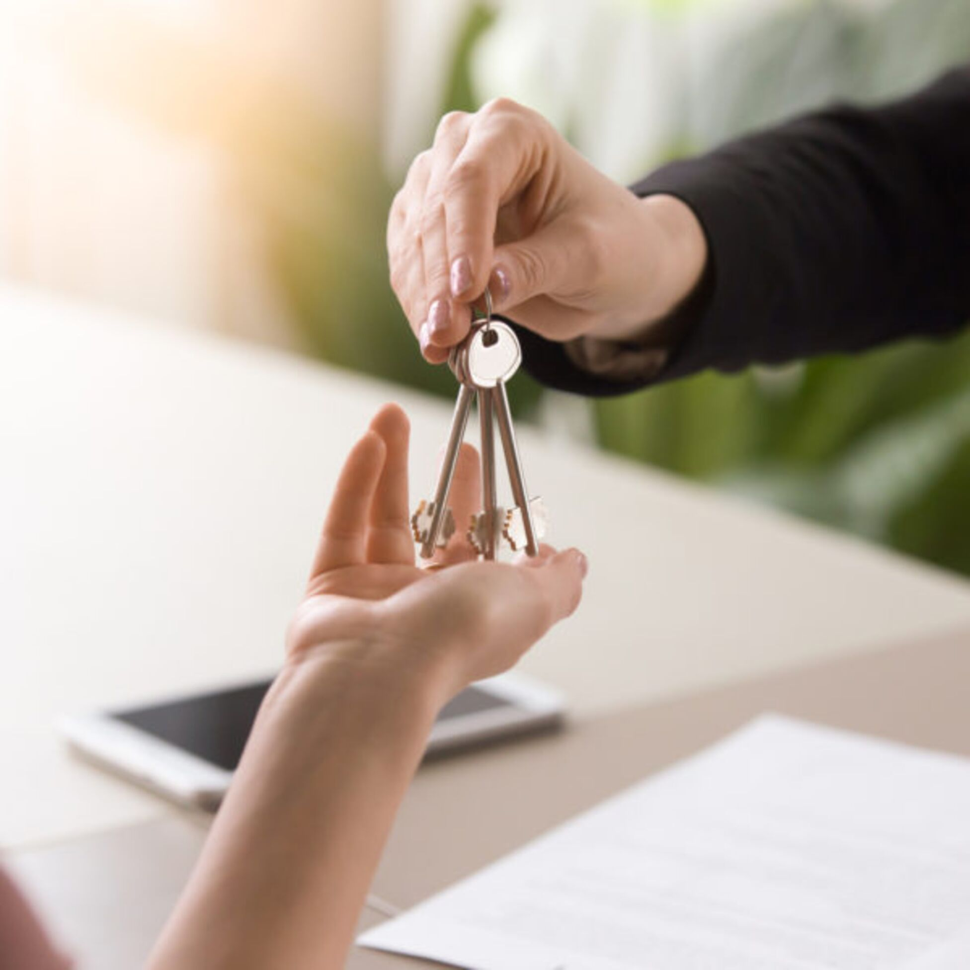 Schlüssel wird von einer Hand in die andere gereicht