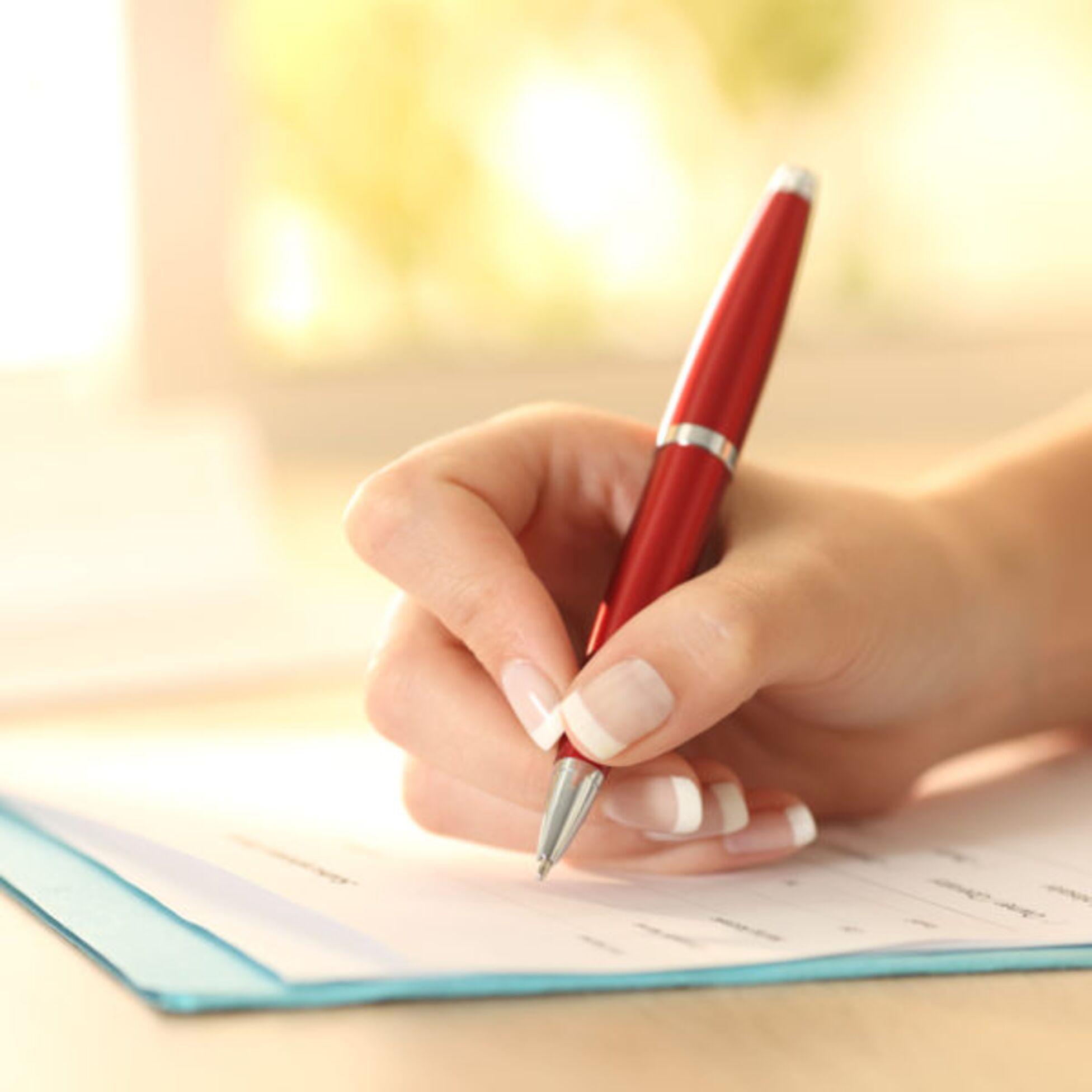 Hand hält Stift und schreibt in Einwohnermeldeamt-Formular