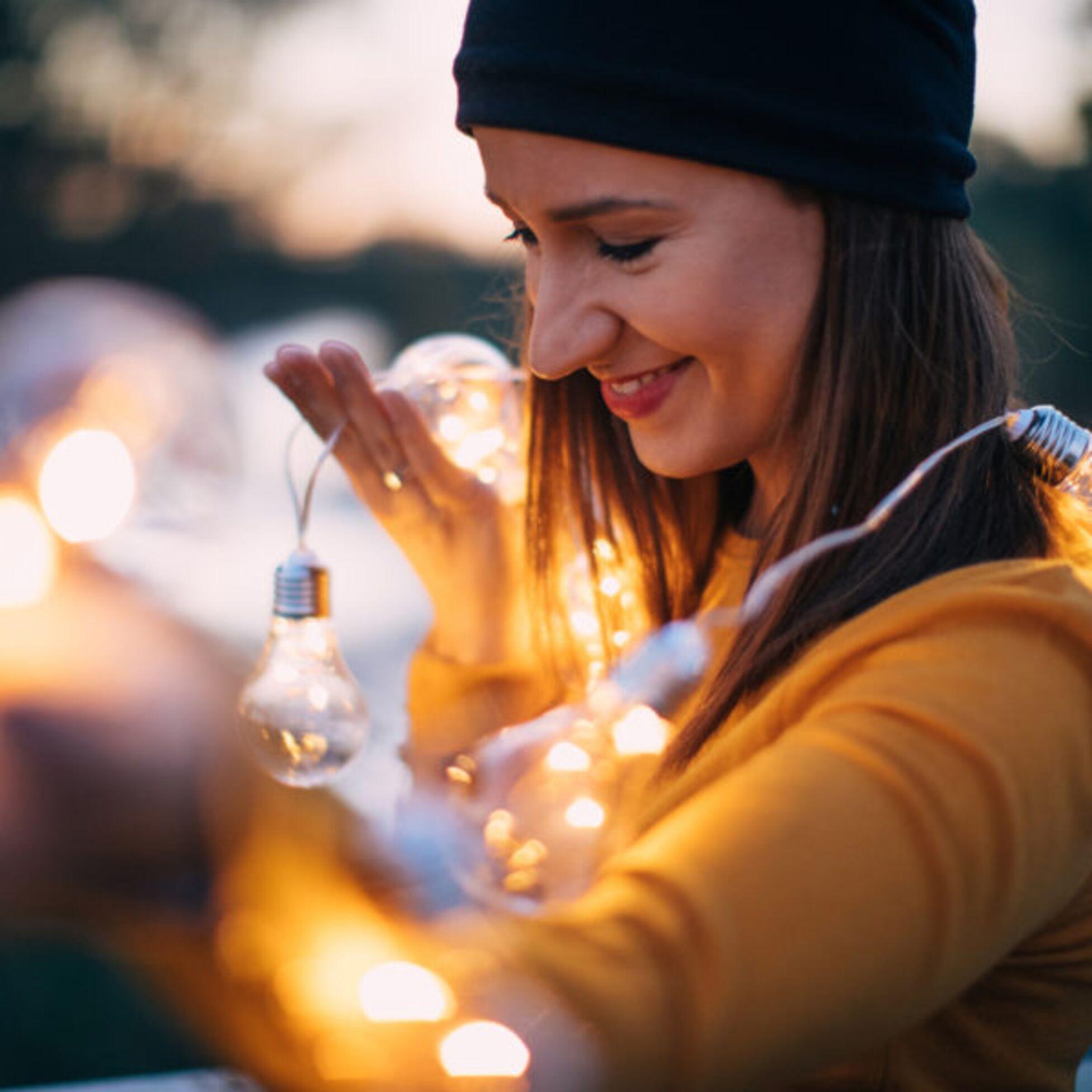 Junge Frau draußen mit leuchtenden Glühlampen.