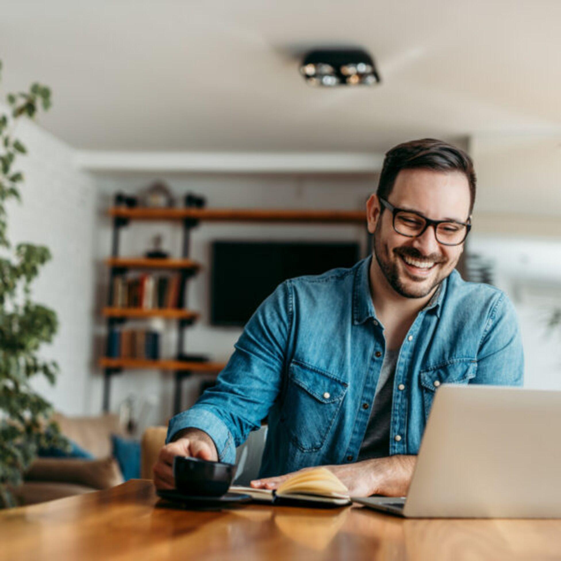 Mann arbeitet lächelnd am Laptop