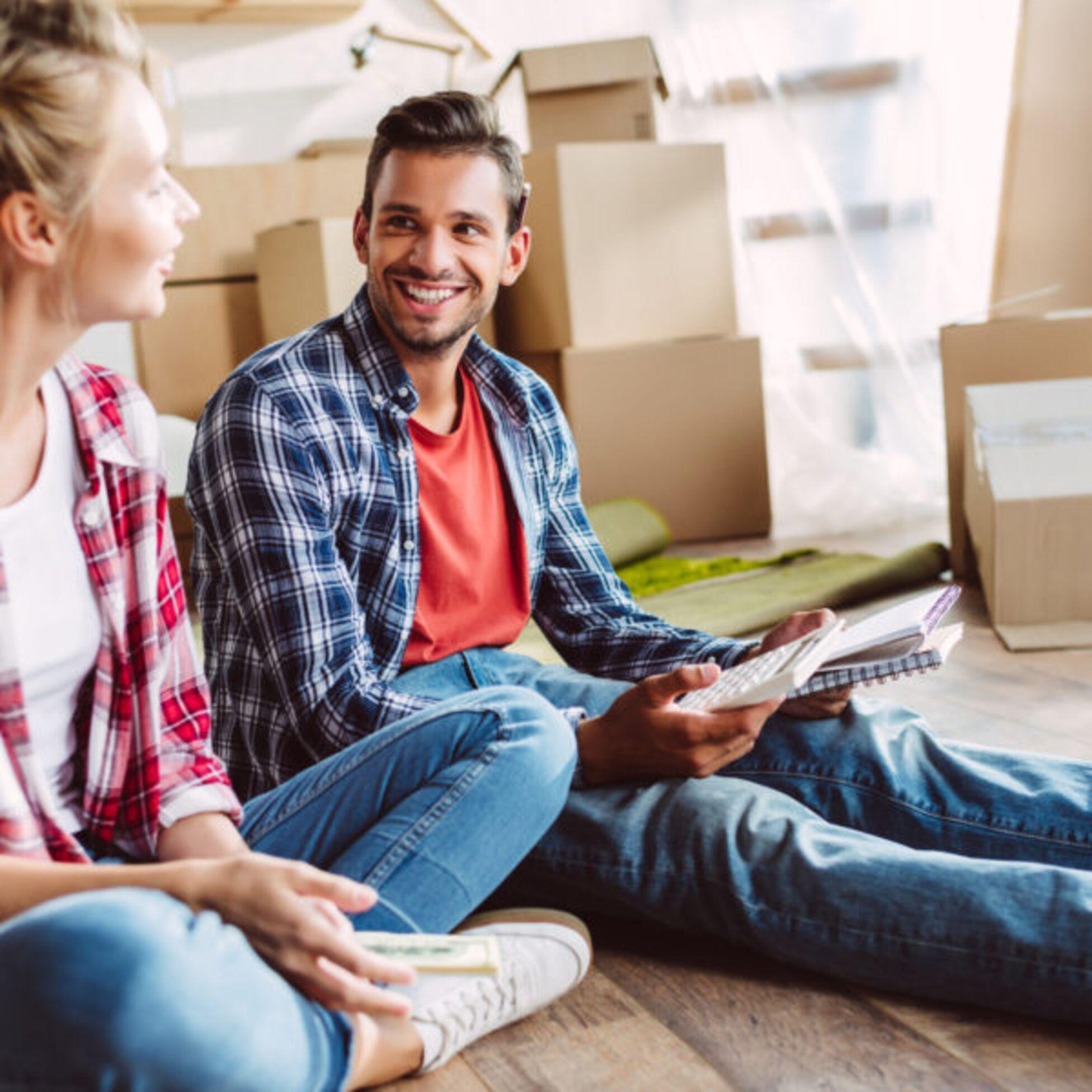 Junges Paar sitzt mit Umzugskartons und Taschenrechner auf dem Fußboden einer Wohnung