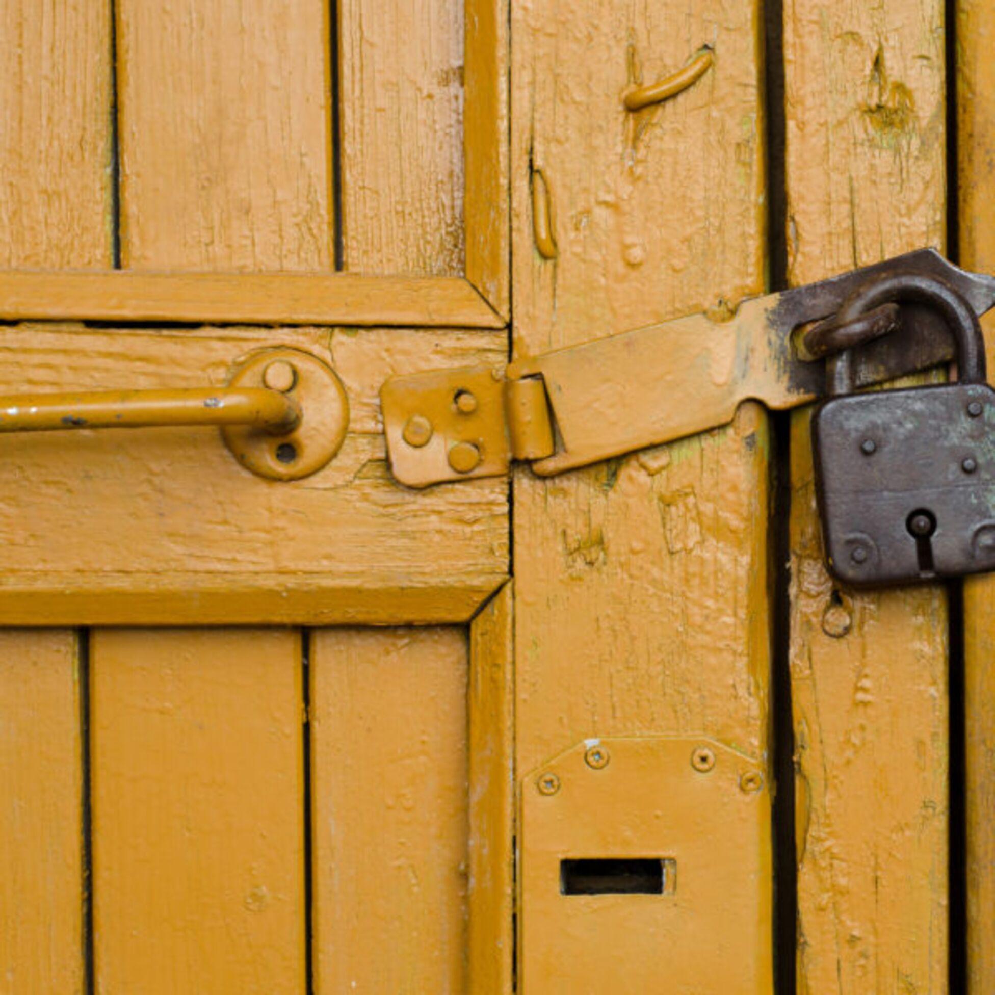 Altes Vorhägeschloss an einer alten, gelben Holztür