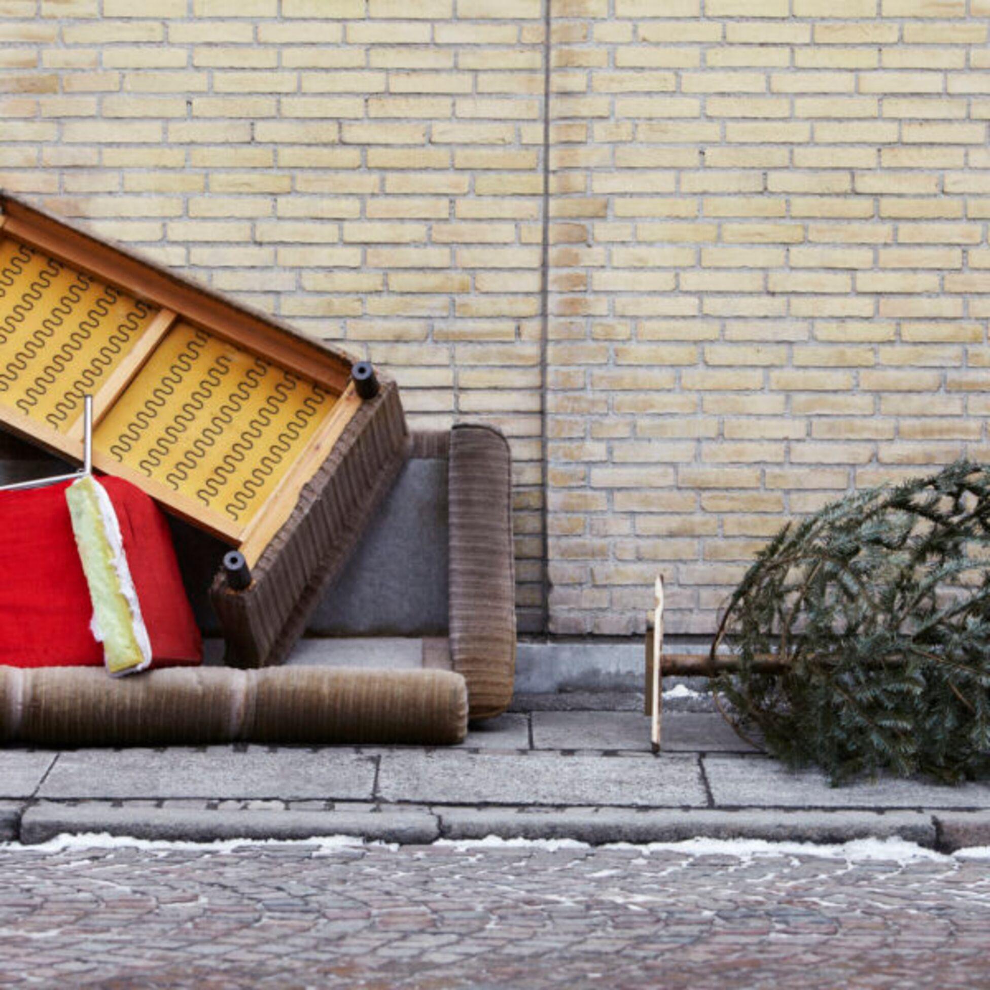 Altes Sofa und Weihnachtsbaum liegen als Sperrmüll auf der Straße