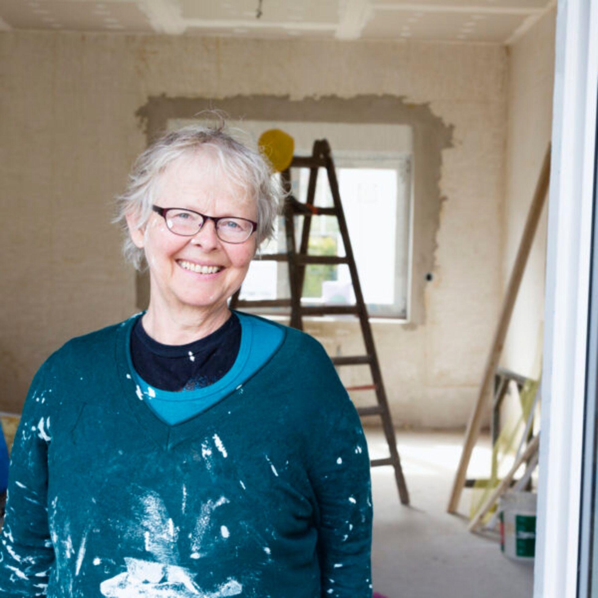 Ältere Frau renoviert fröhlich eine Wohnung