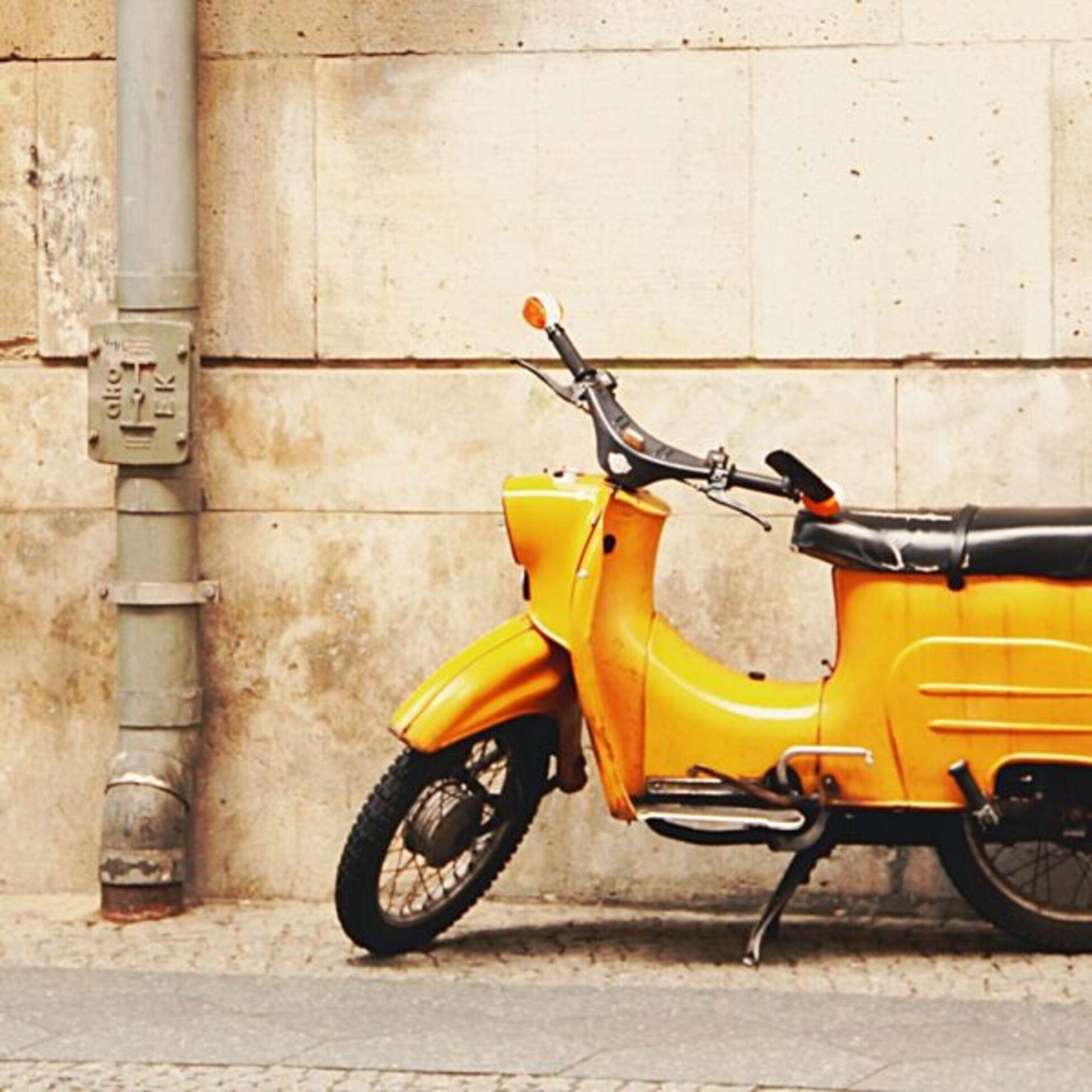 Alter, gelber Roller vor einer Sandsteinmauer