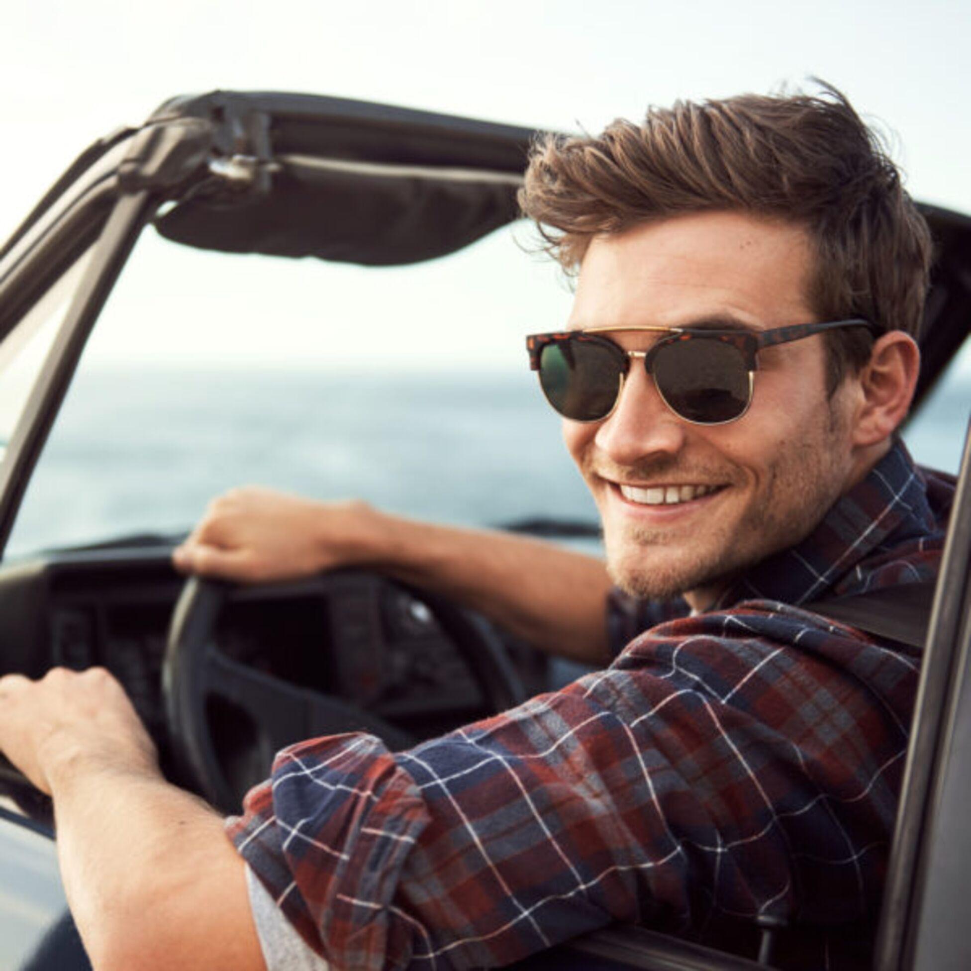 Junger Mann am Steuer eines Cabrio