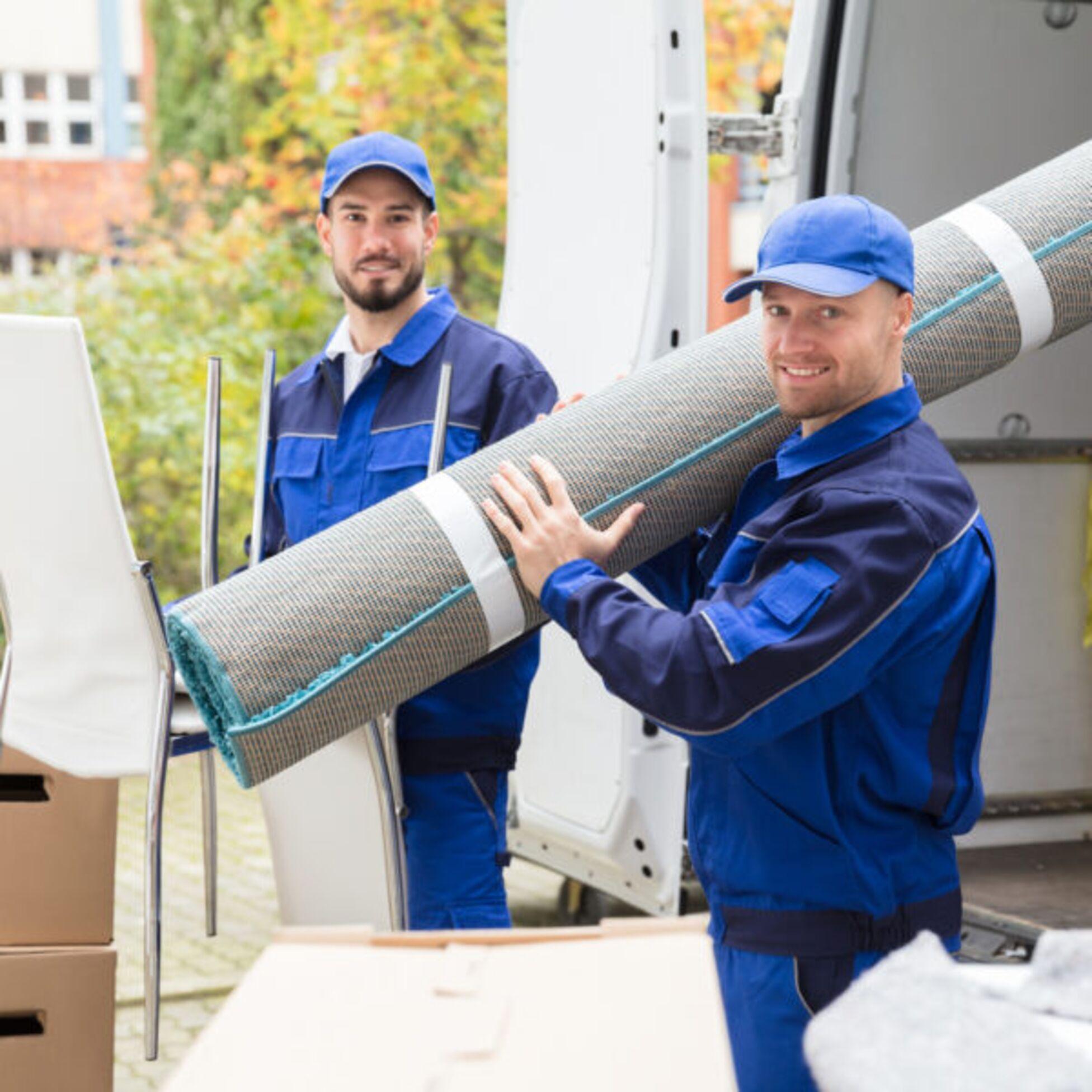 Zwei Möbelpacker laden Umzugsgut aus einem Transporter aus