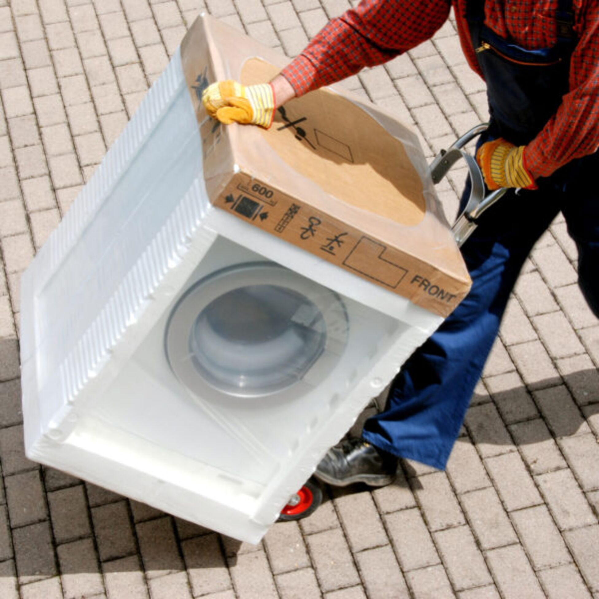 Mann transportiert Waschmaschine bei Umzug auf Sackkarre