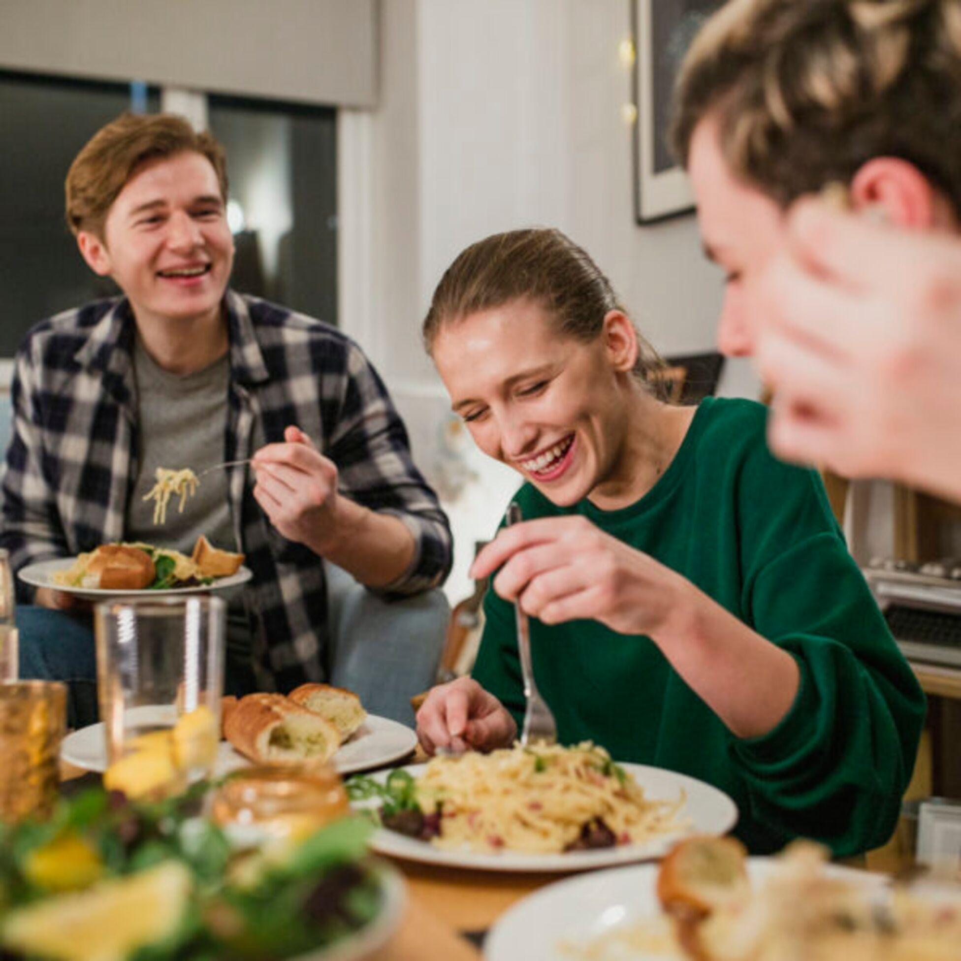 Gruppe junger Menschen in einer WG isst gemeinsam.