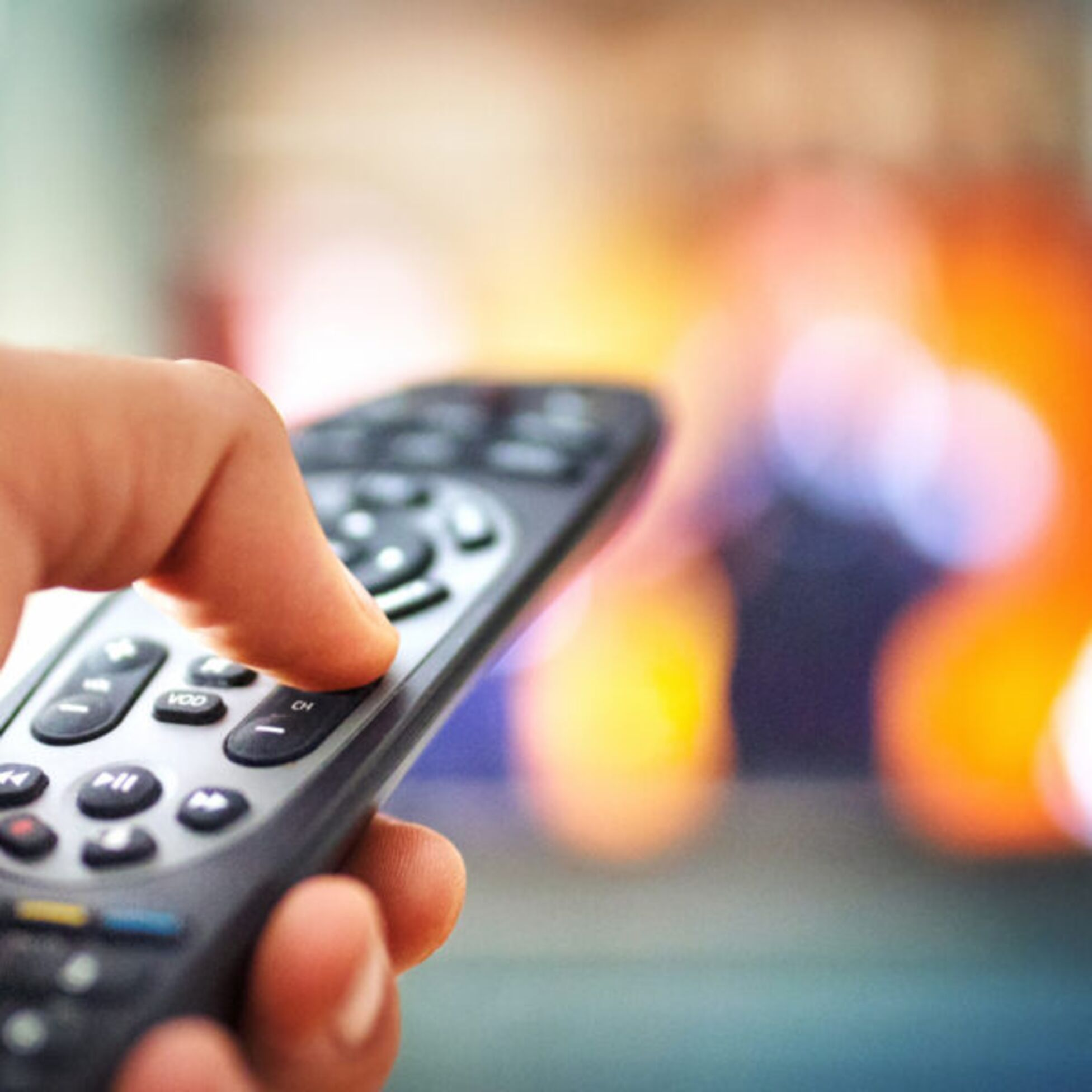 Mann schaltet Fernseher mit Fernbedienung aus