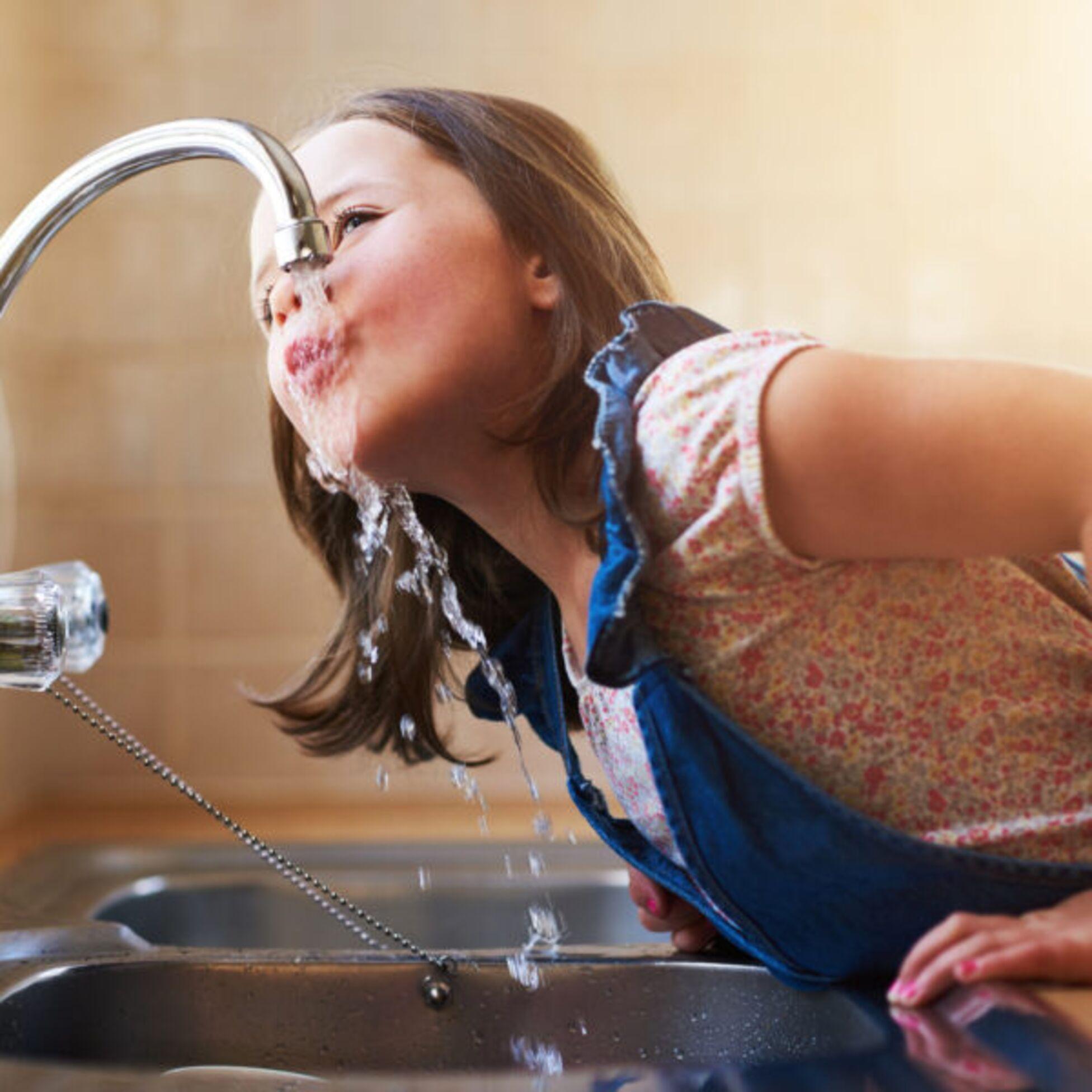 Mädchen trinkt Wasser aus der Leitung