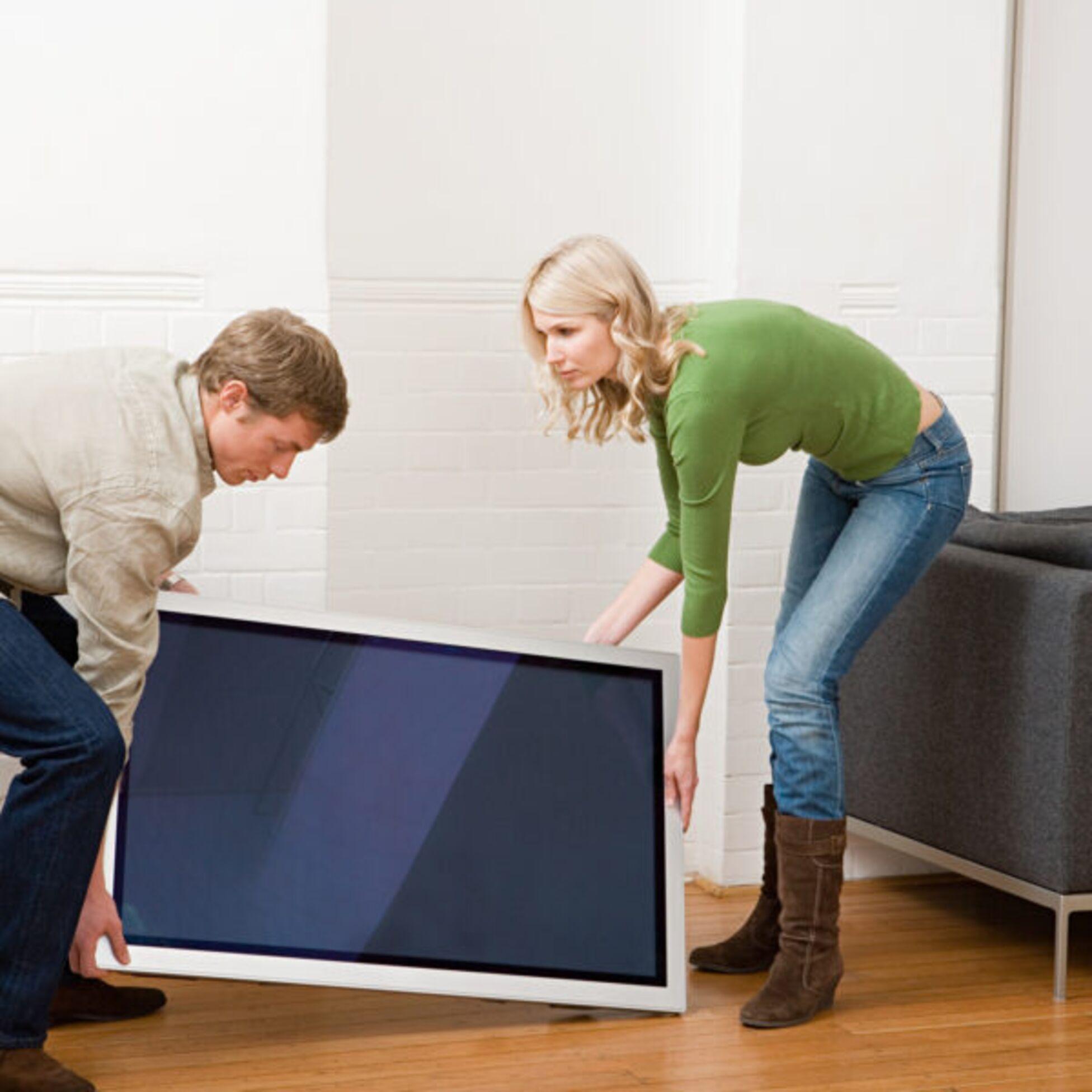 Mann und Frau tragen einen Fernseher