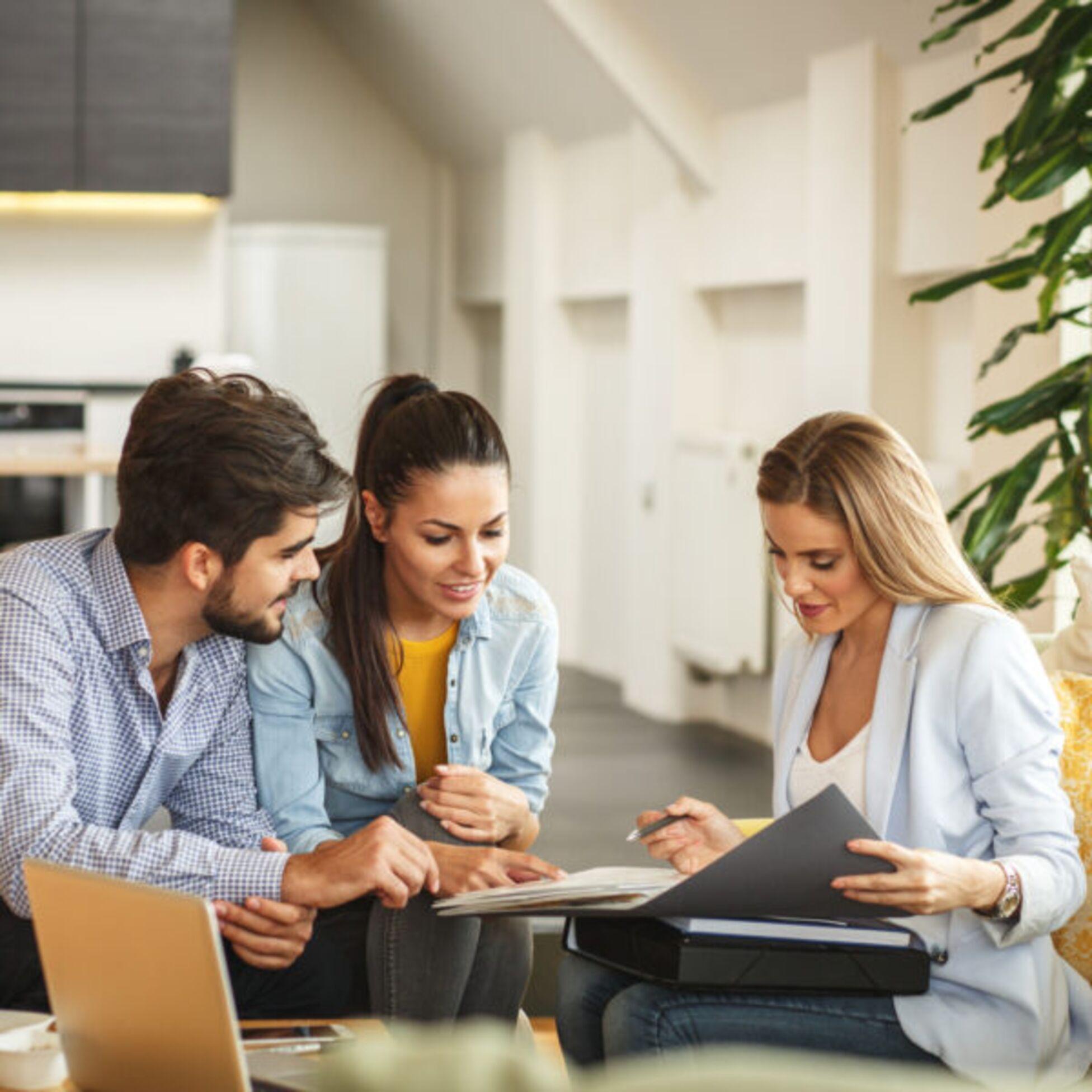 Drei Personen sitzen in einer Wohnung und schauen in einen Aktenordner