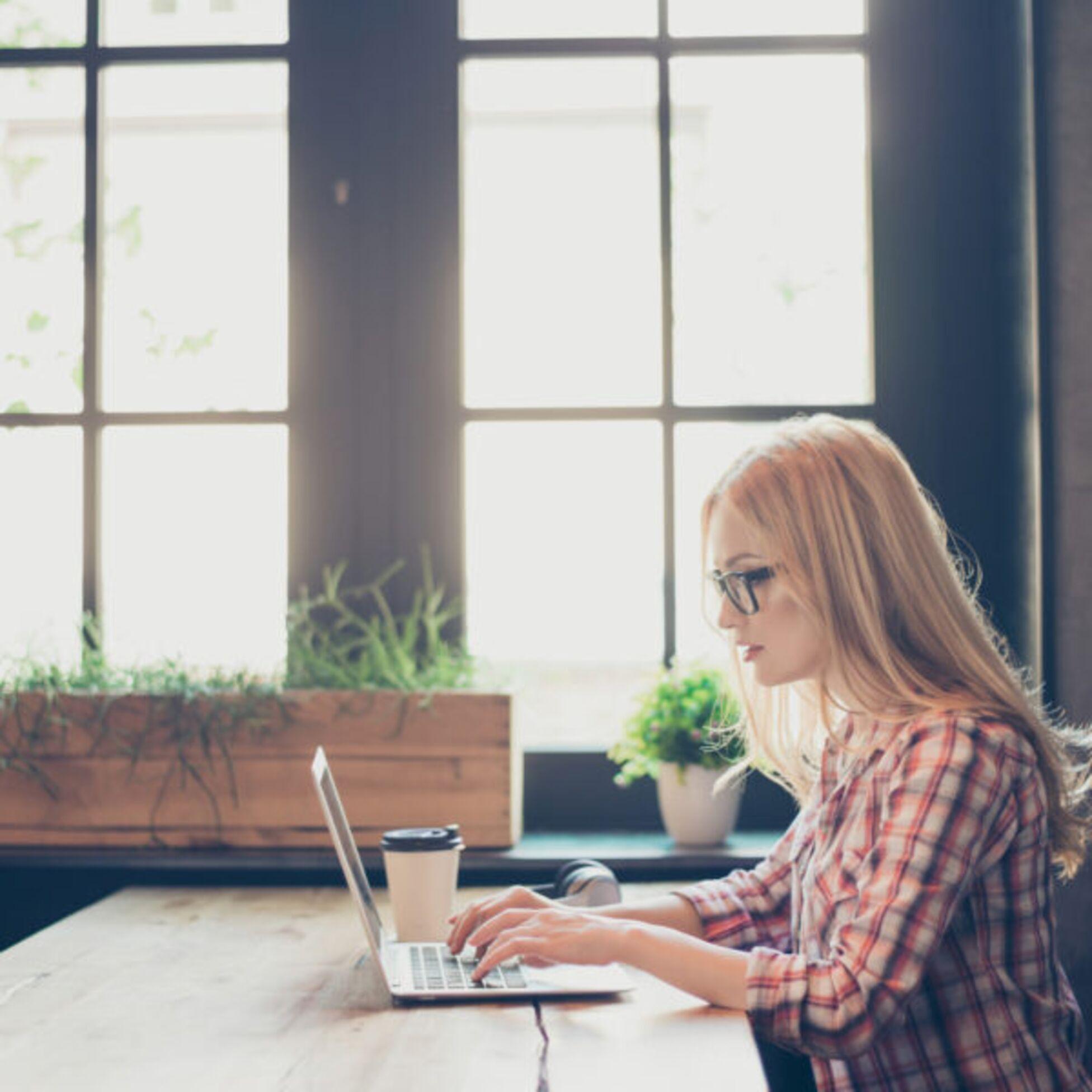 Frau arbeitet an einem Tisch an einem Laptop
