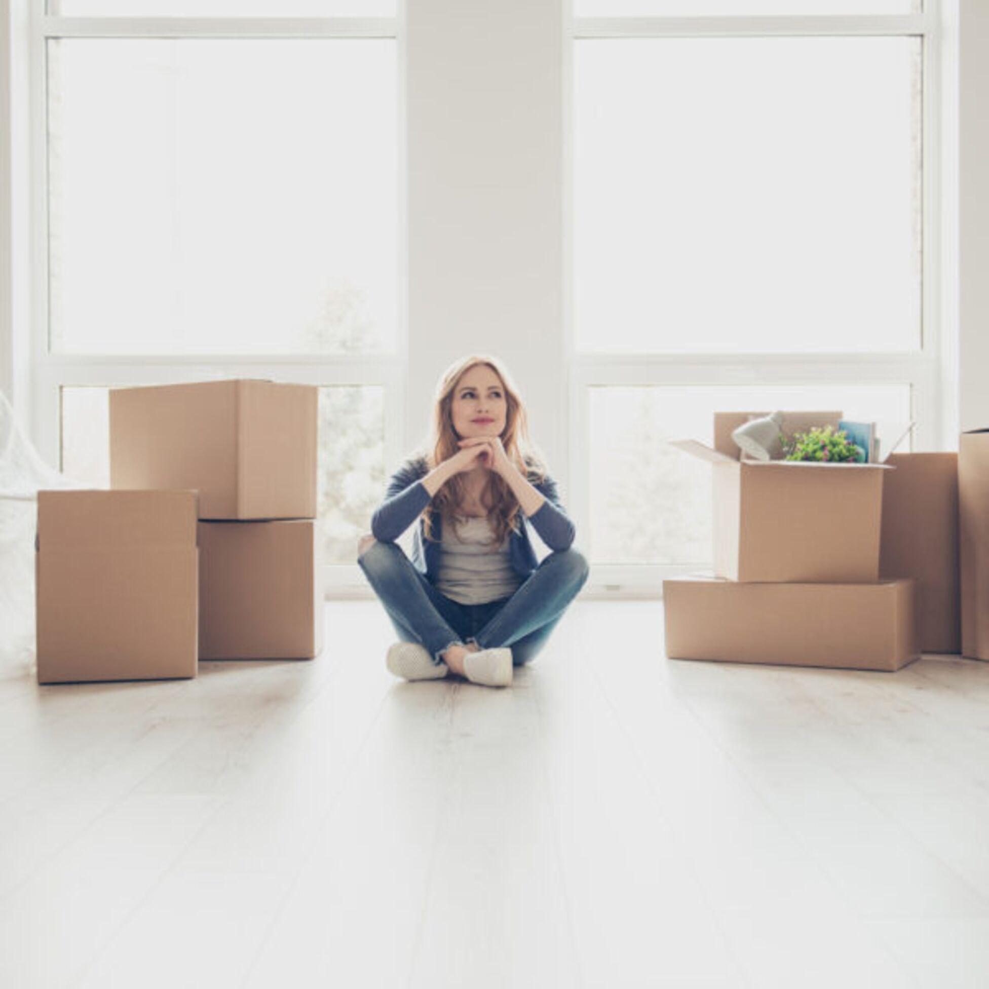 Junge Frau sitzt in leerer Wohnung, Umzugskartons stehen neben ihr.