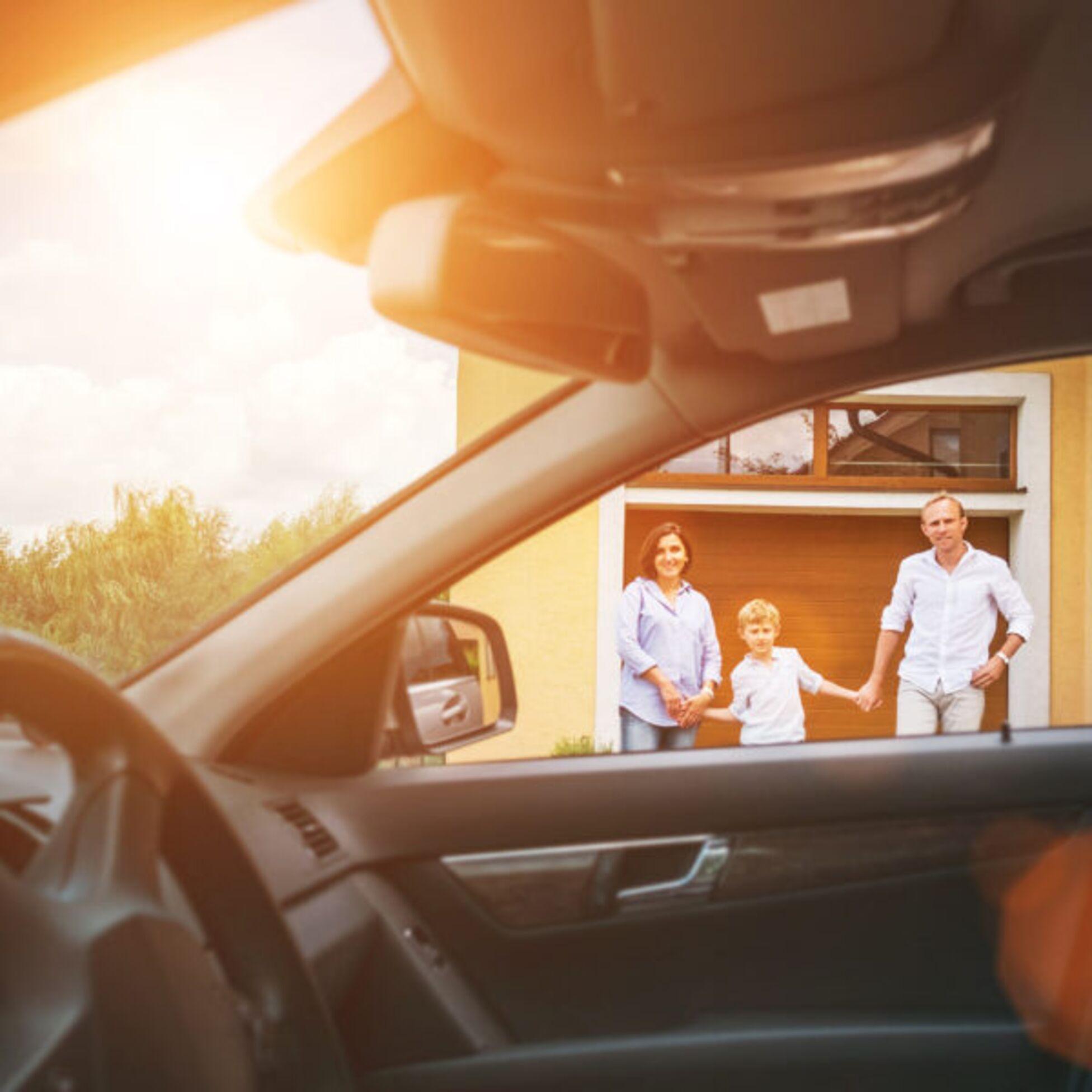 Ein Auto und eine Familie vor ihrem Haus