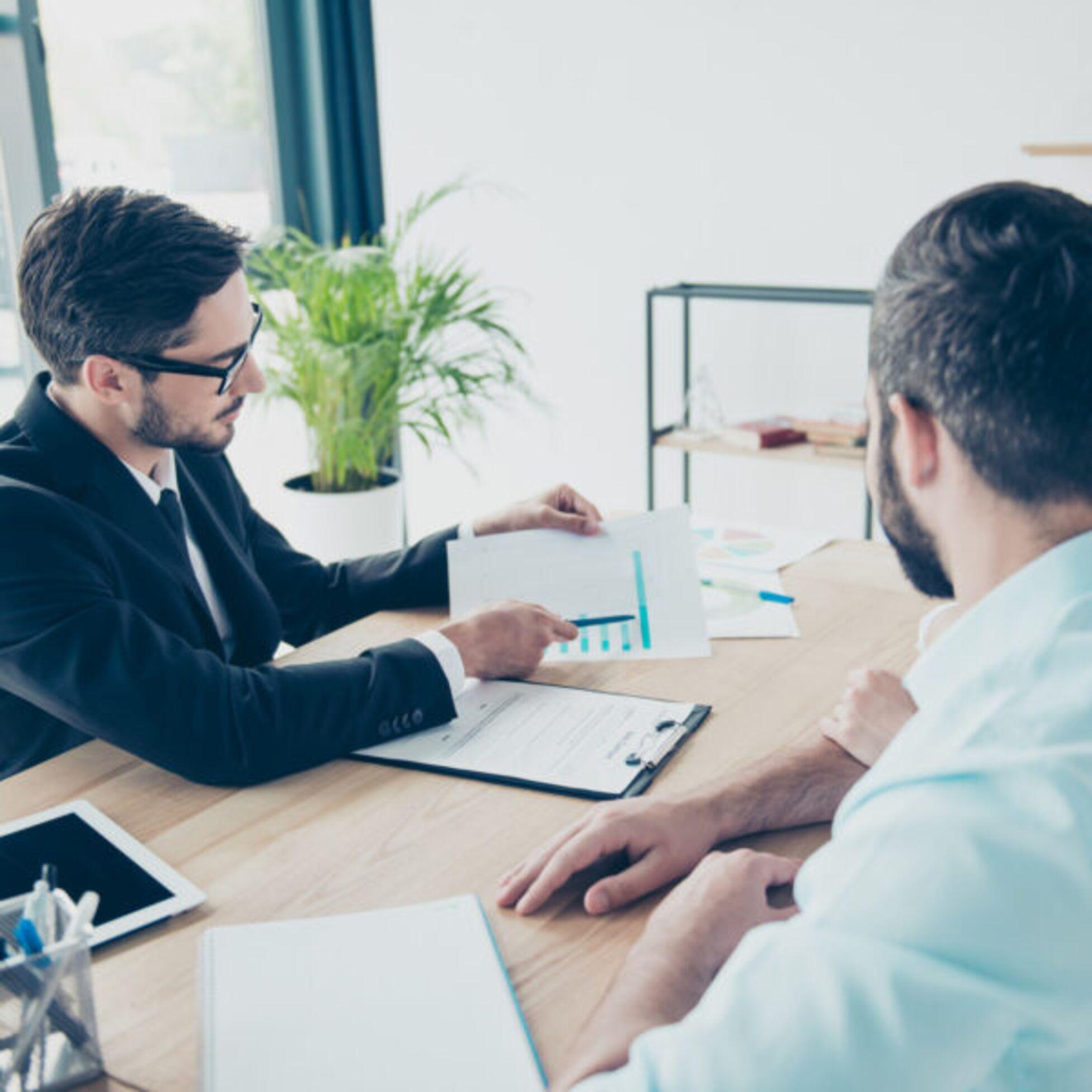 Mann zeigt Paar Mietvertrag an einem Schreibtisch