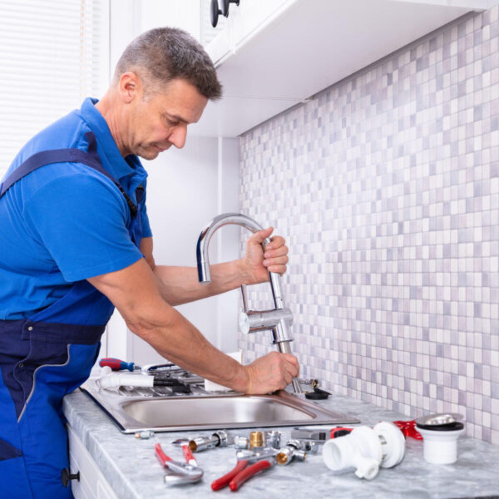 Handwerker repariert Wasserhahn