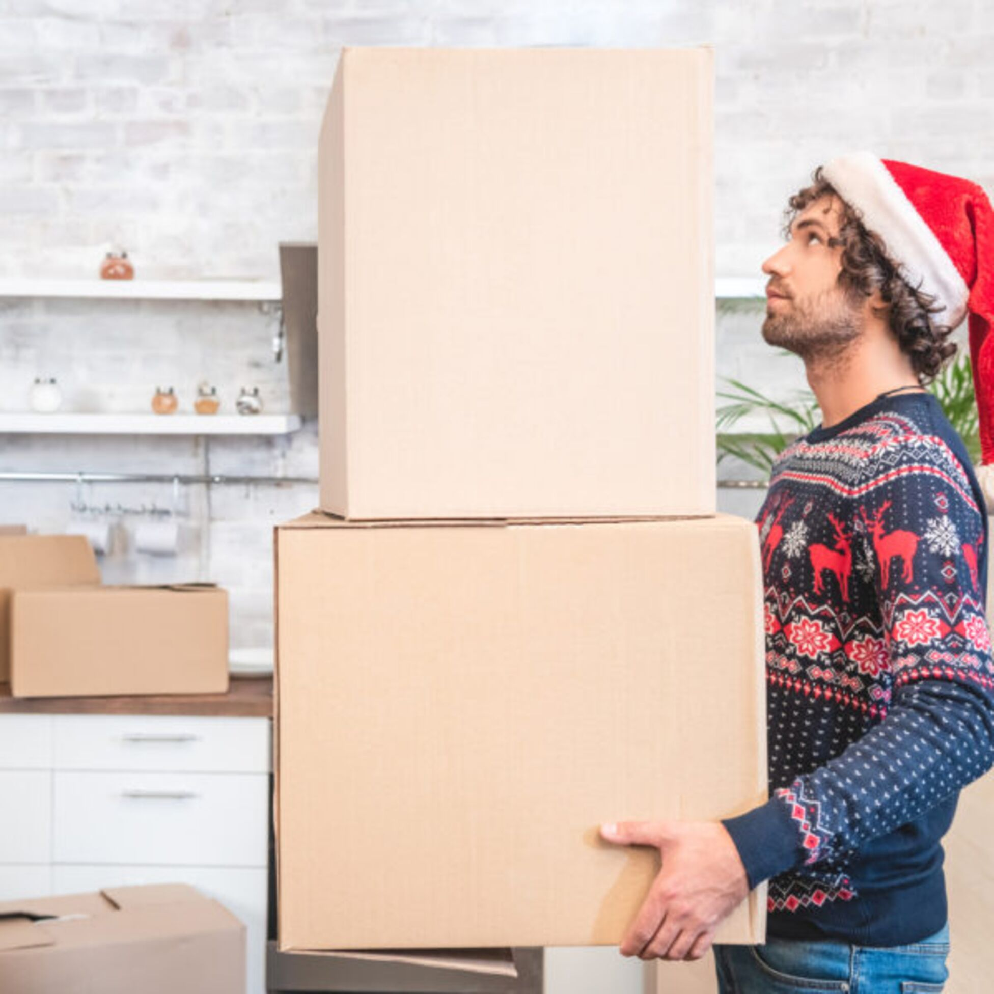 Mann trägt vor Weihnachten Umzugskartons