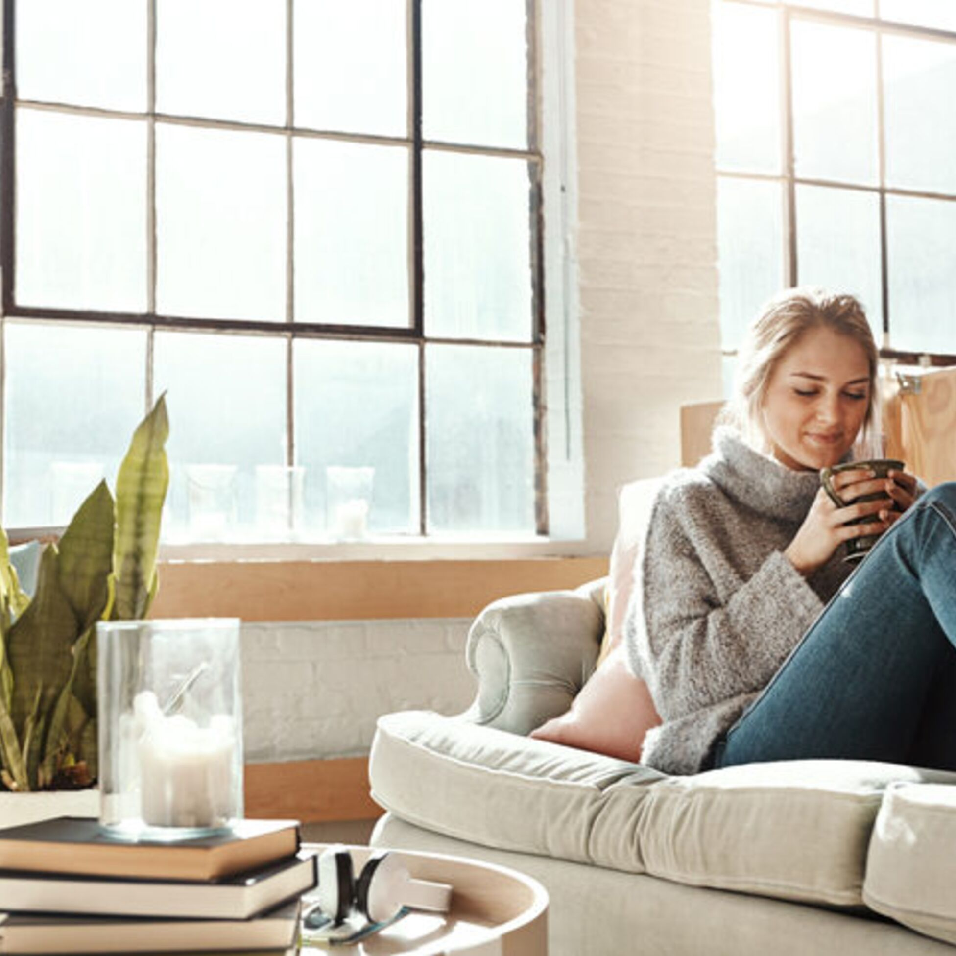 Frau wohnt alleine und sitzt auf der Couch