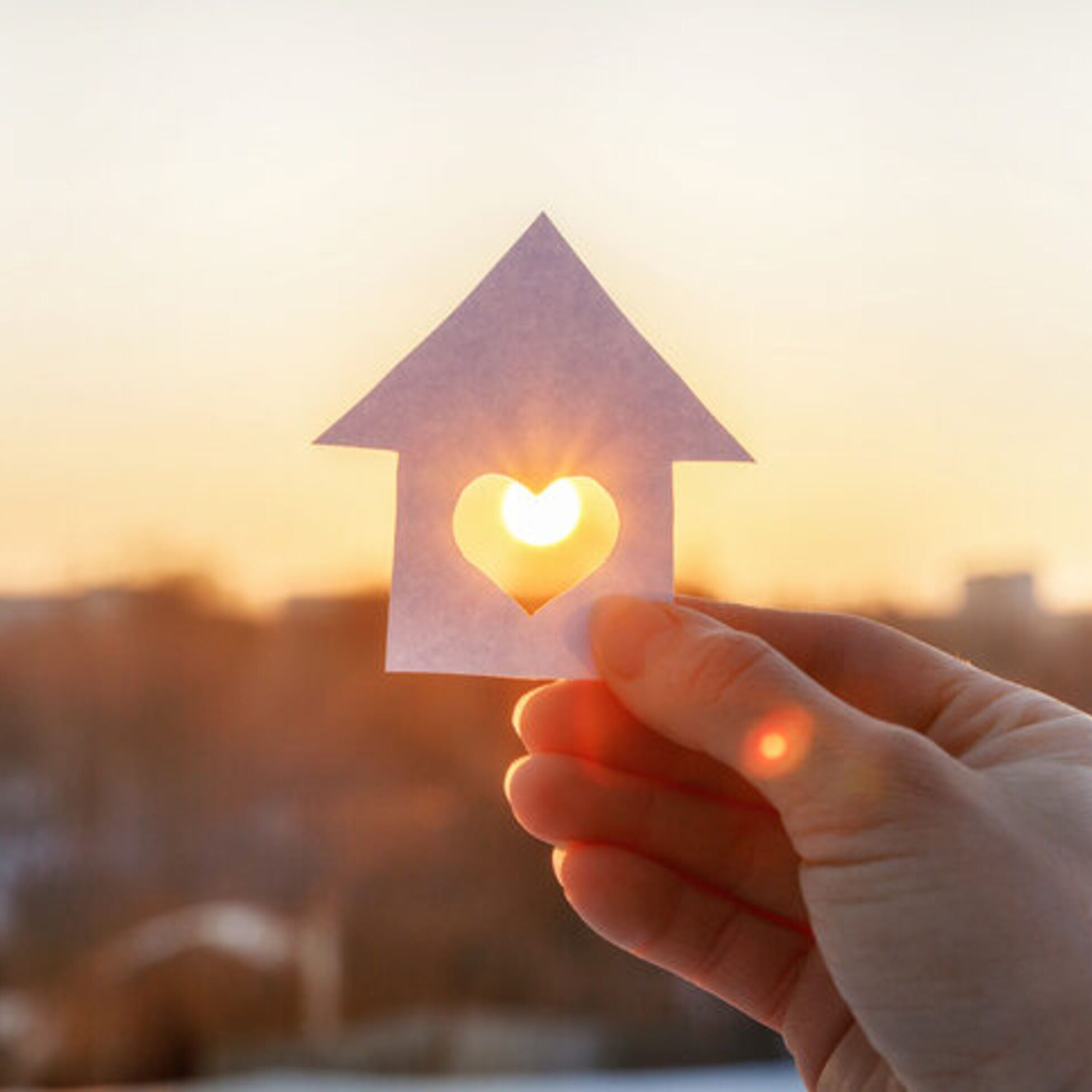 Hand hält ein Papierhaus mit Herz