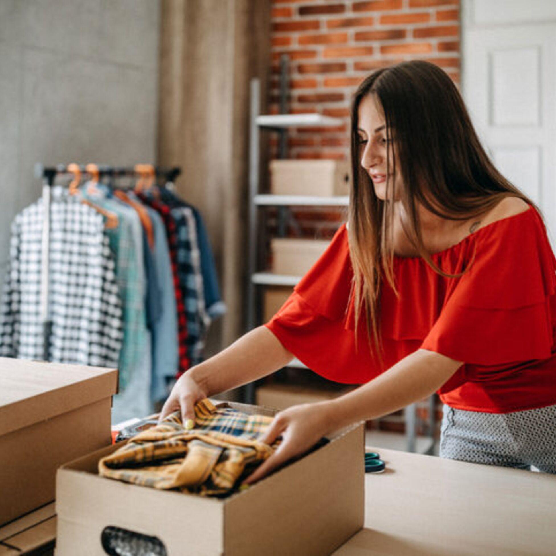 Frau packt Kleider ein