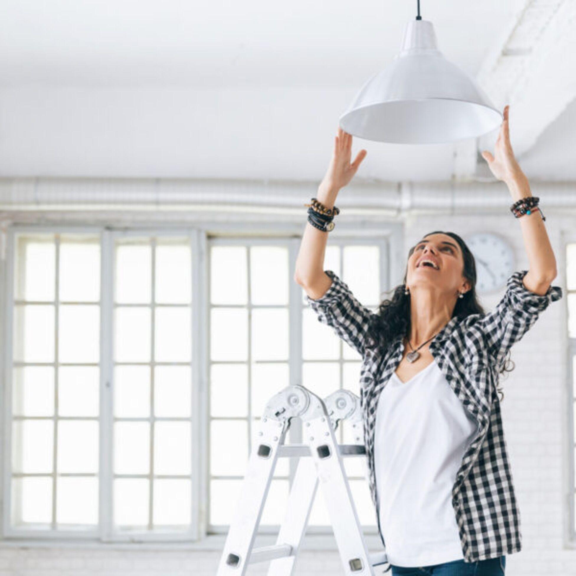 Frau hängt Lampe auf